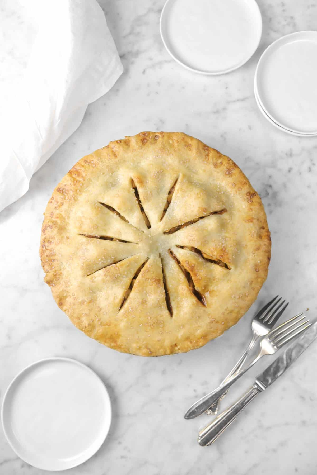 apple pie with three plates and forks