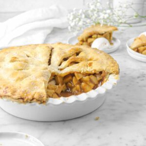 apple pie with two slices behind with flowers and white napkin