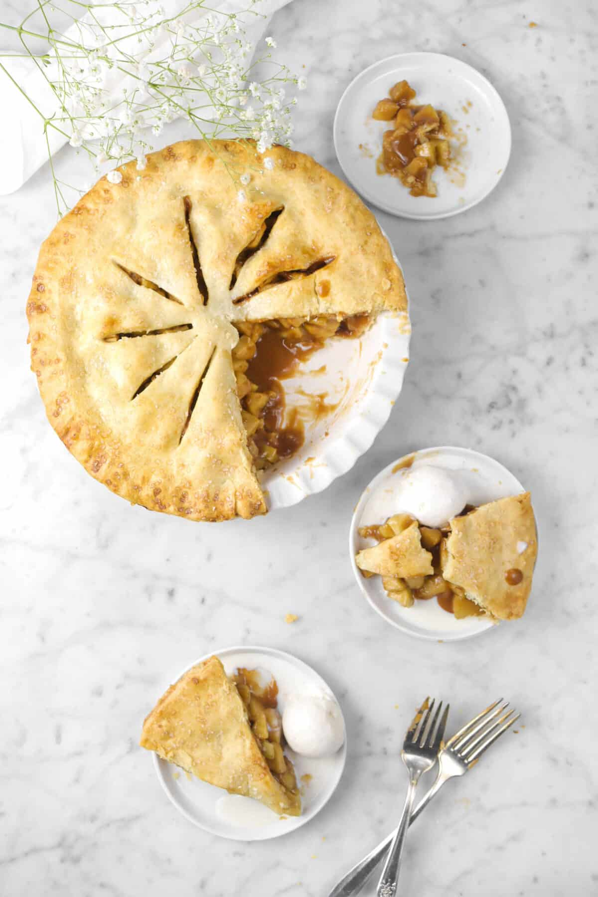 apple pie on marble counter with two slices taken out with white flowers