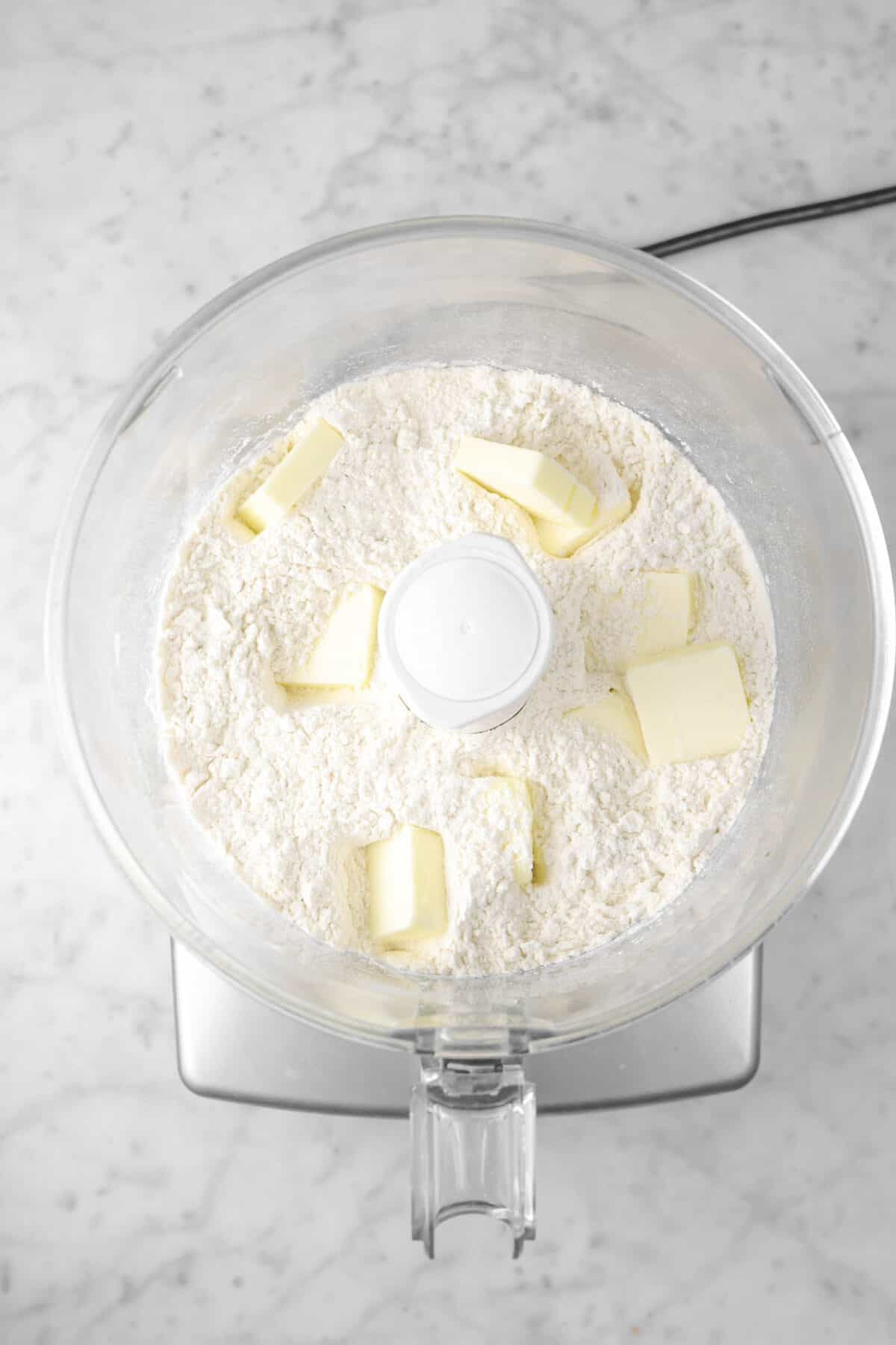 nine pads of butter added to flour in food processor