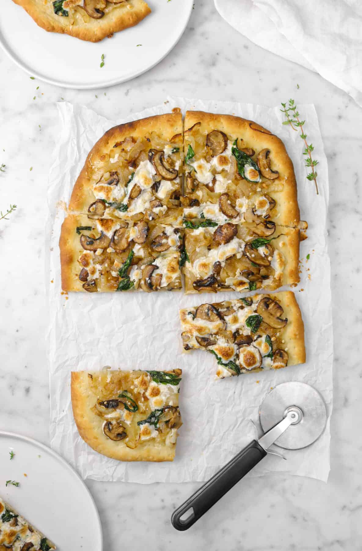 flatbread on parchment with thyme sprigs, pizza cutter, and two pieces on white plates