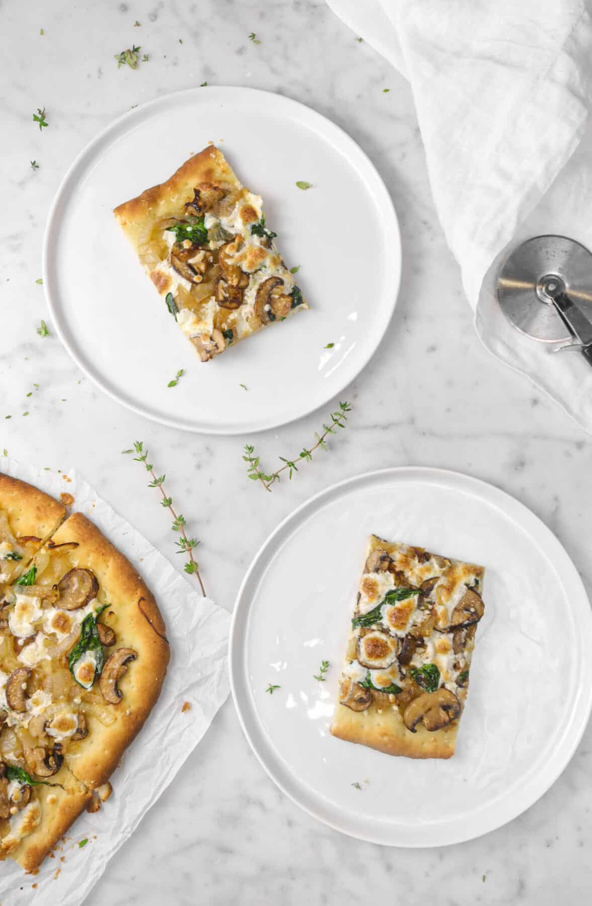 two slices of mushroom flatbread on white plates with thyme sprigs and napkin