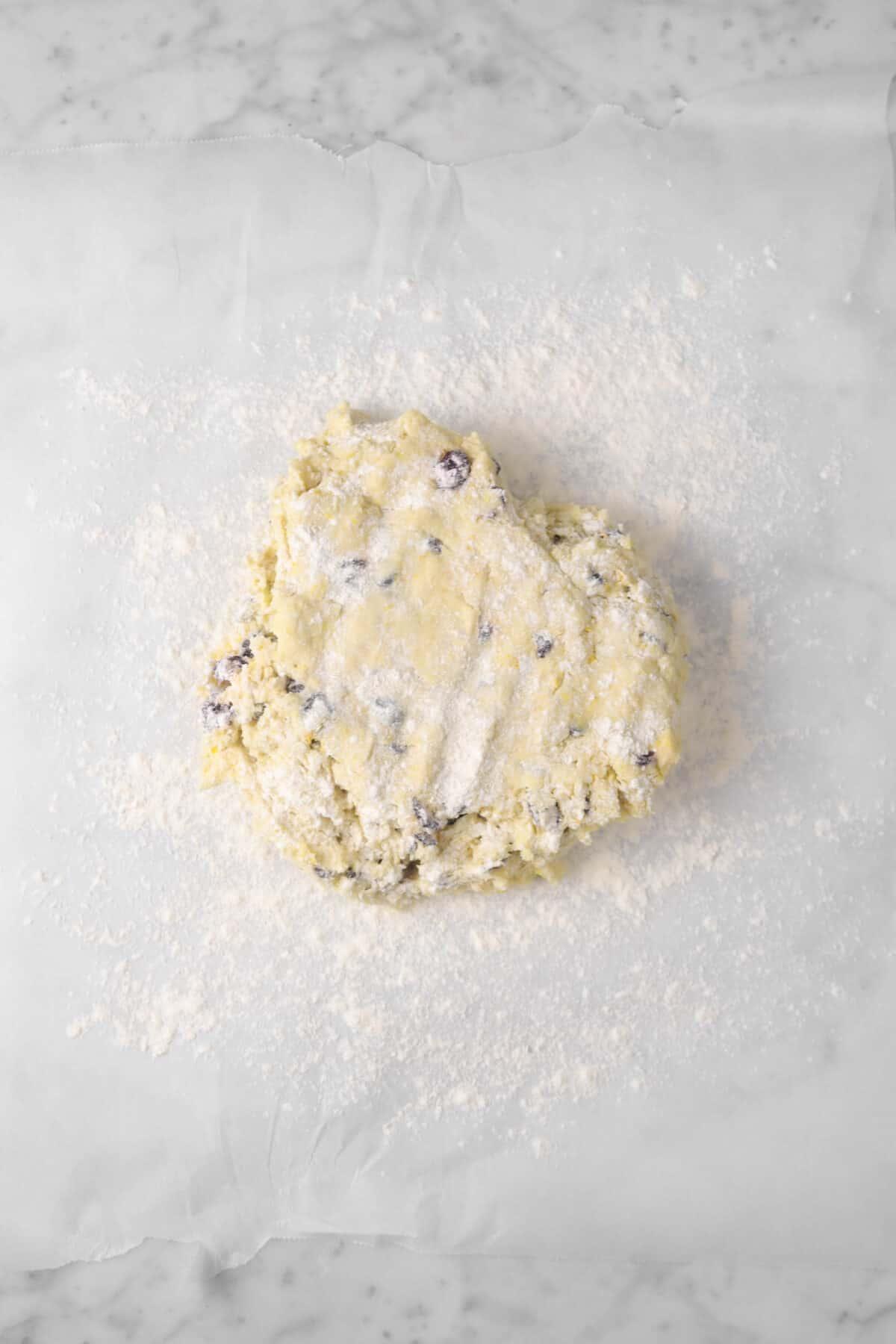 scone dough on parchment with flour