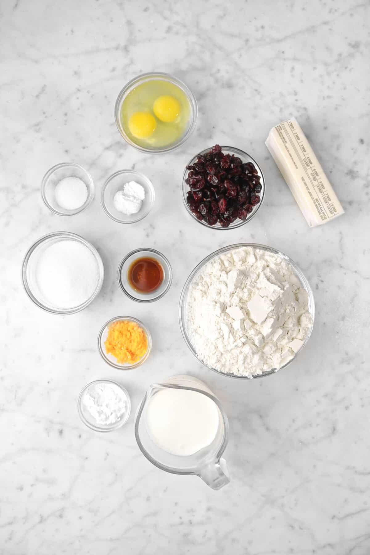 eggs, dried cranberries, butter, baking powder, salt, sugar, vanilla, orange zest, baking soda, milk, and flower on a marble counter