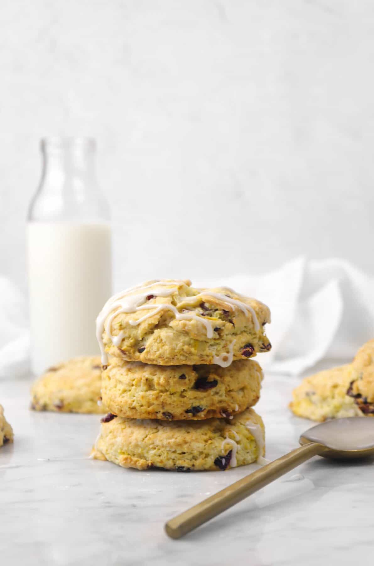 three orange cranberry scones stacked with a gold spoon and glass of milk