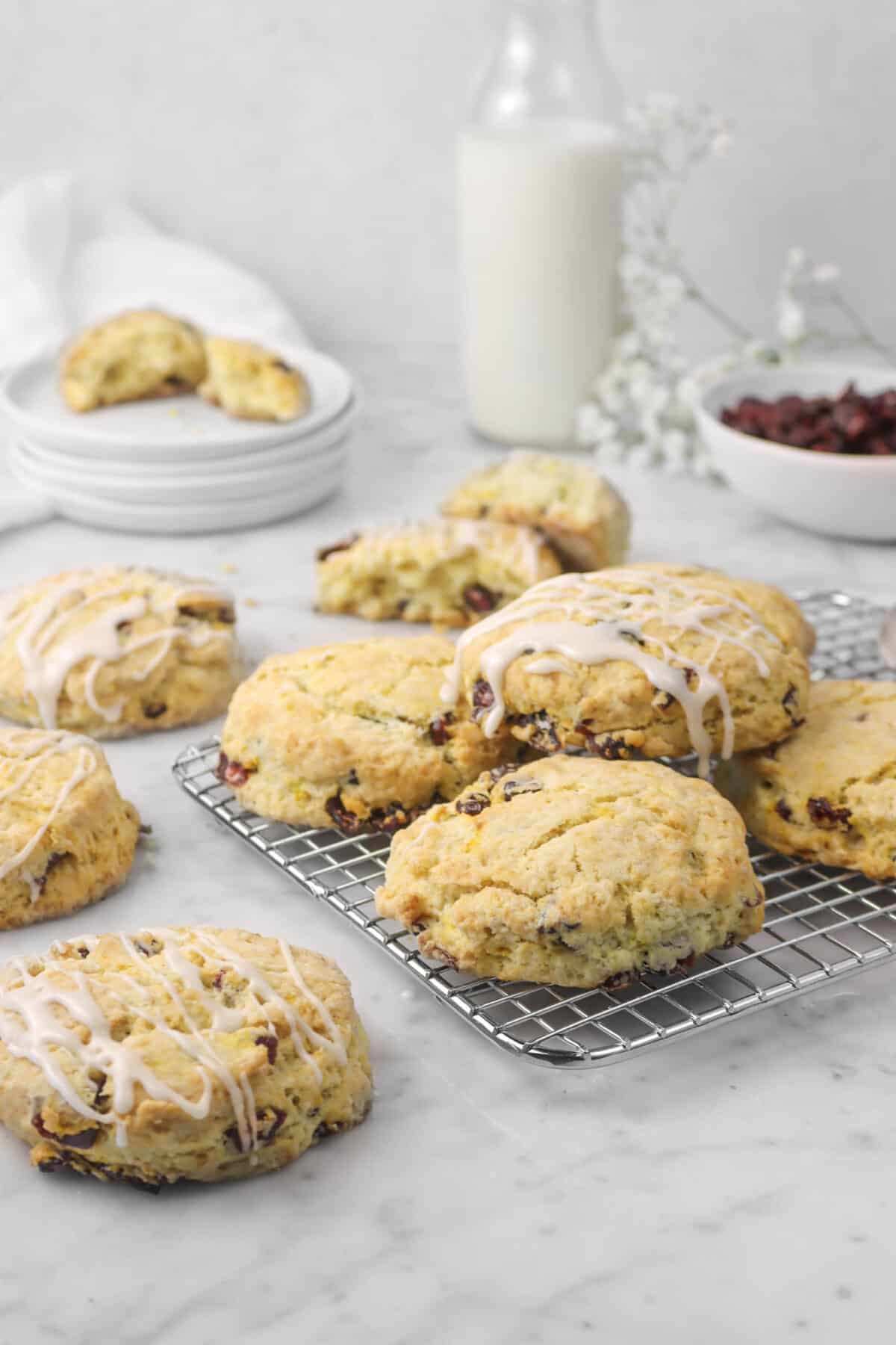 eight scones with two broken open, a bowl of cranberries, flowers, and milk