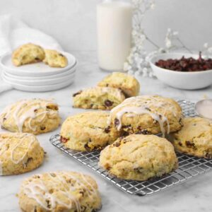 four scones on a cooling rack with three beside, a glass of milk, bowl of cranberries, and flowers behind