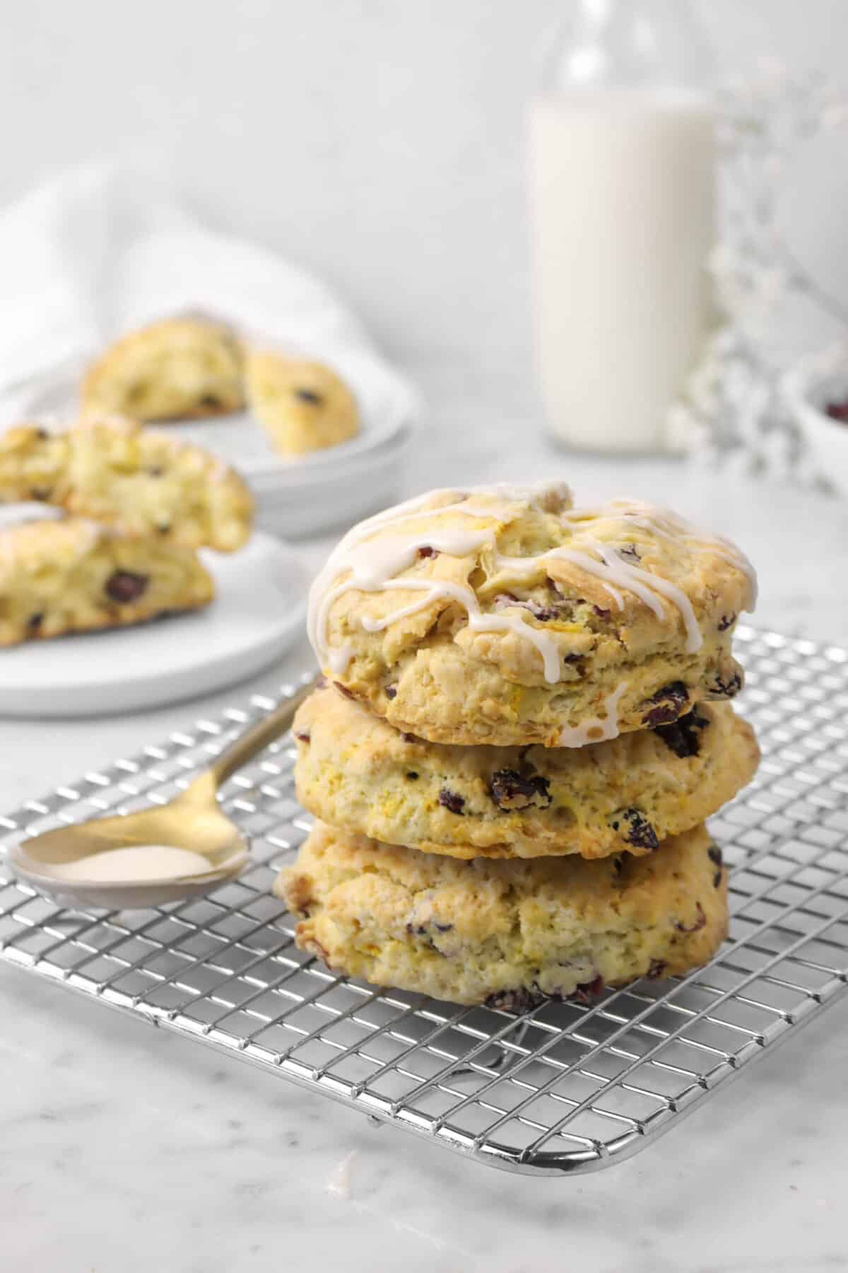 three scones stacked on a wire cooling rack with a gold spoon, more scones behind, and a glass of milk