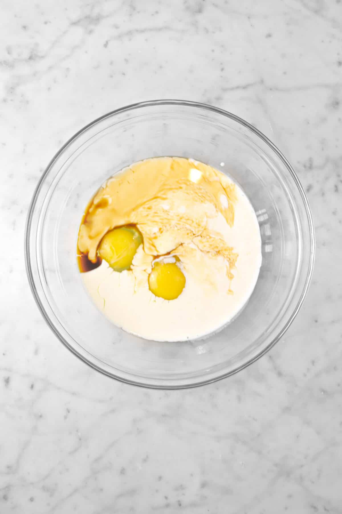 eggs, milk, and vanilla in a glass bowl
