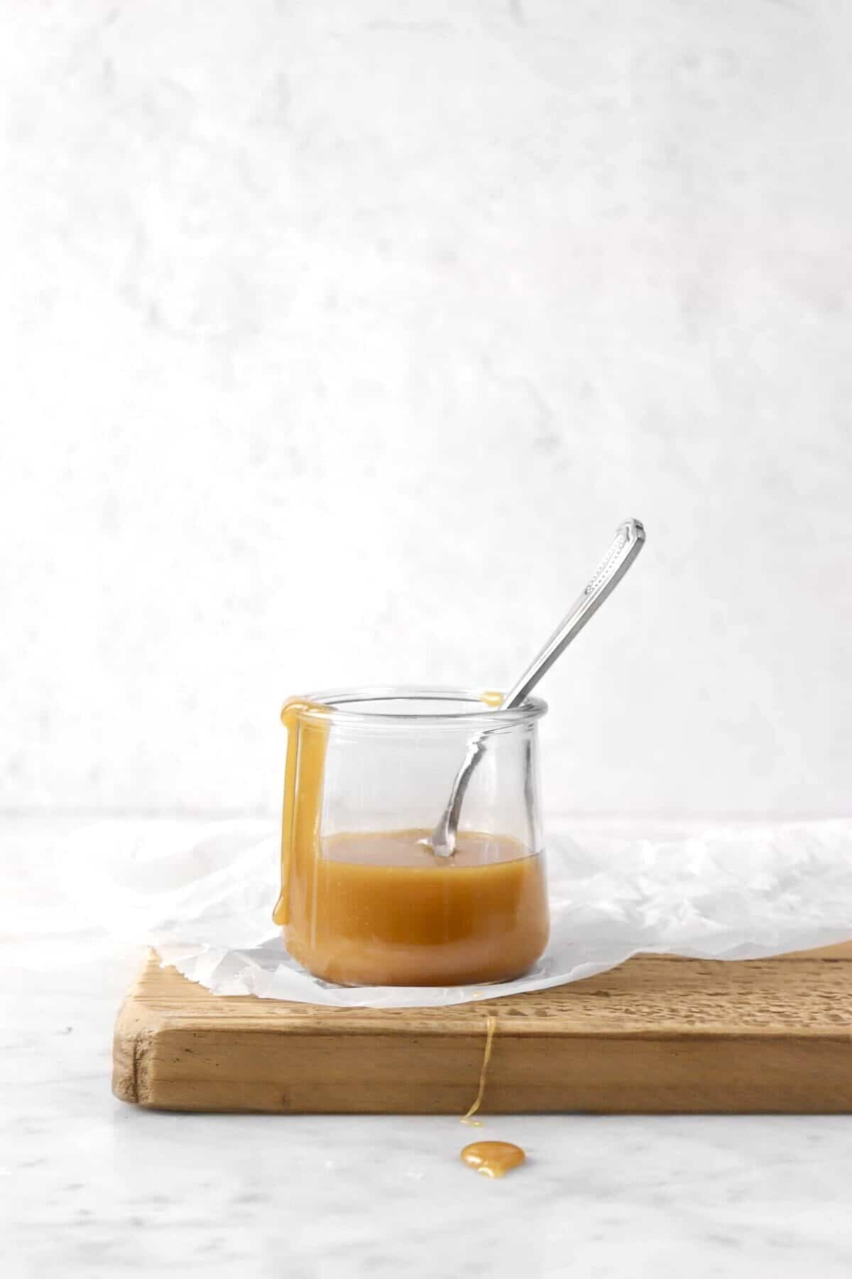 a jar of caramel sauce on a wood board with caramel running over the edge