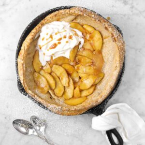 cinnamon apple dutch baby with powdered sugar, spoons, a white napkin, and plates