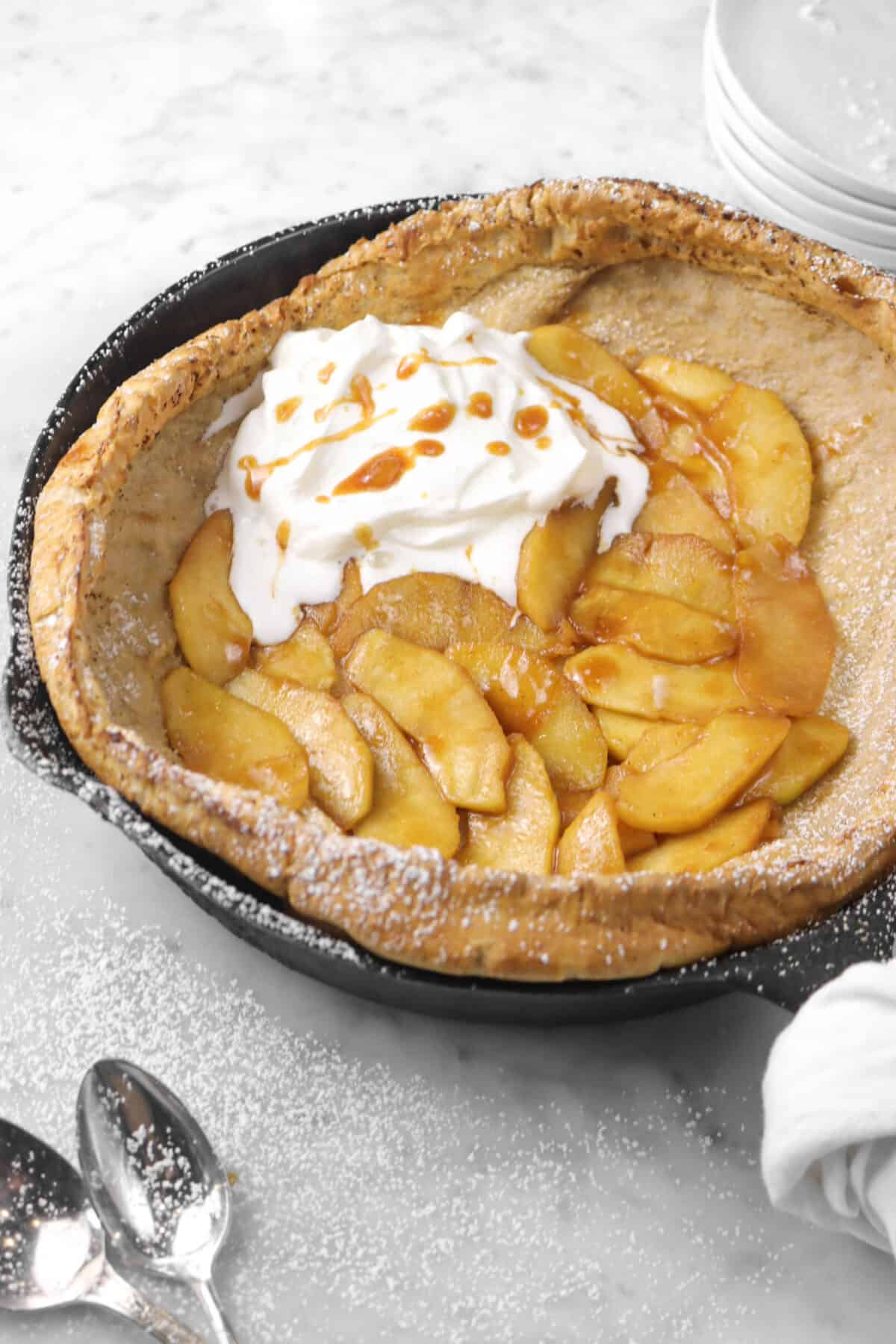 apple dutch baby on a marble counter with whipped cream and powdered sugar