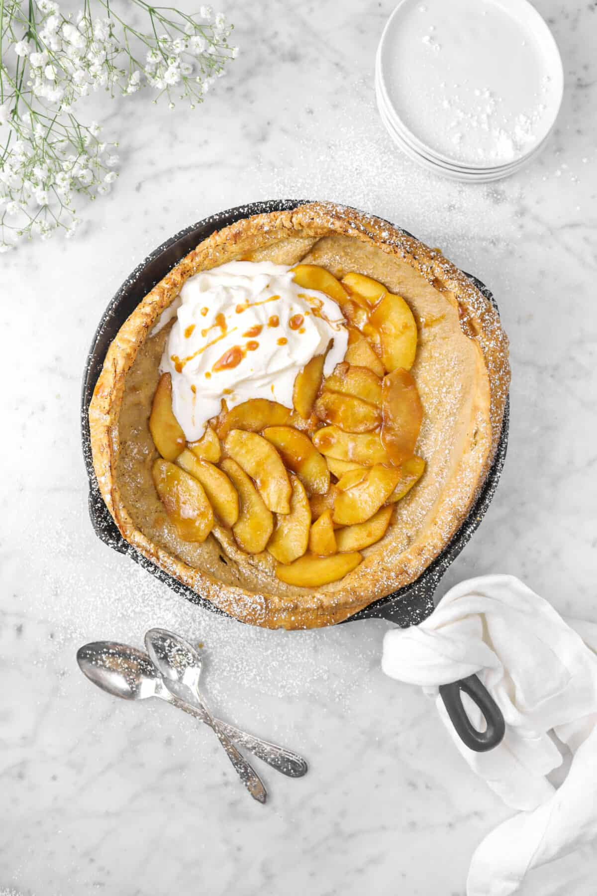apple dutch baby with two spoons, flowers, napkin, and plates