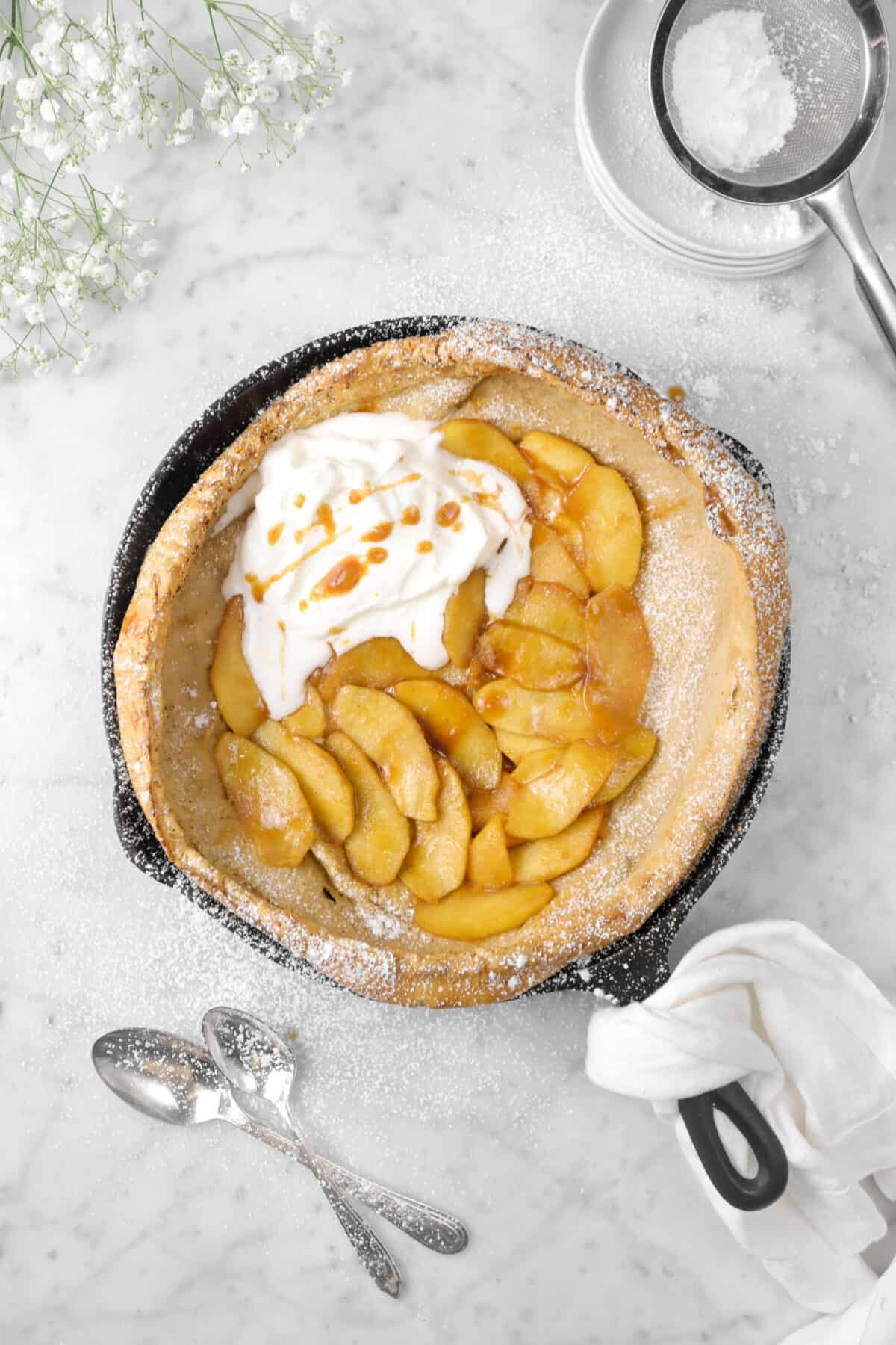 apple dutch baby with powdered sugar, flowers, and a napkin