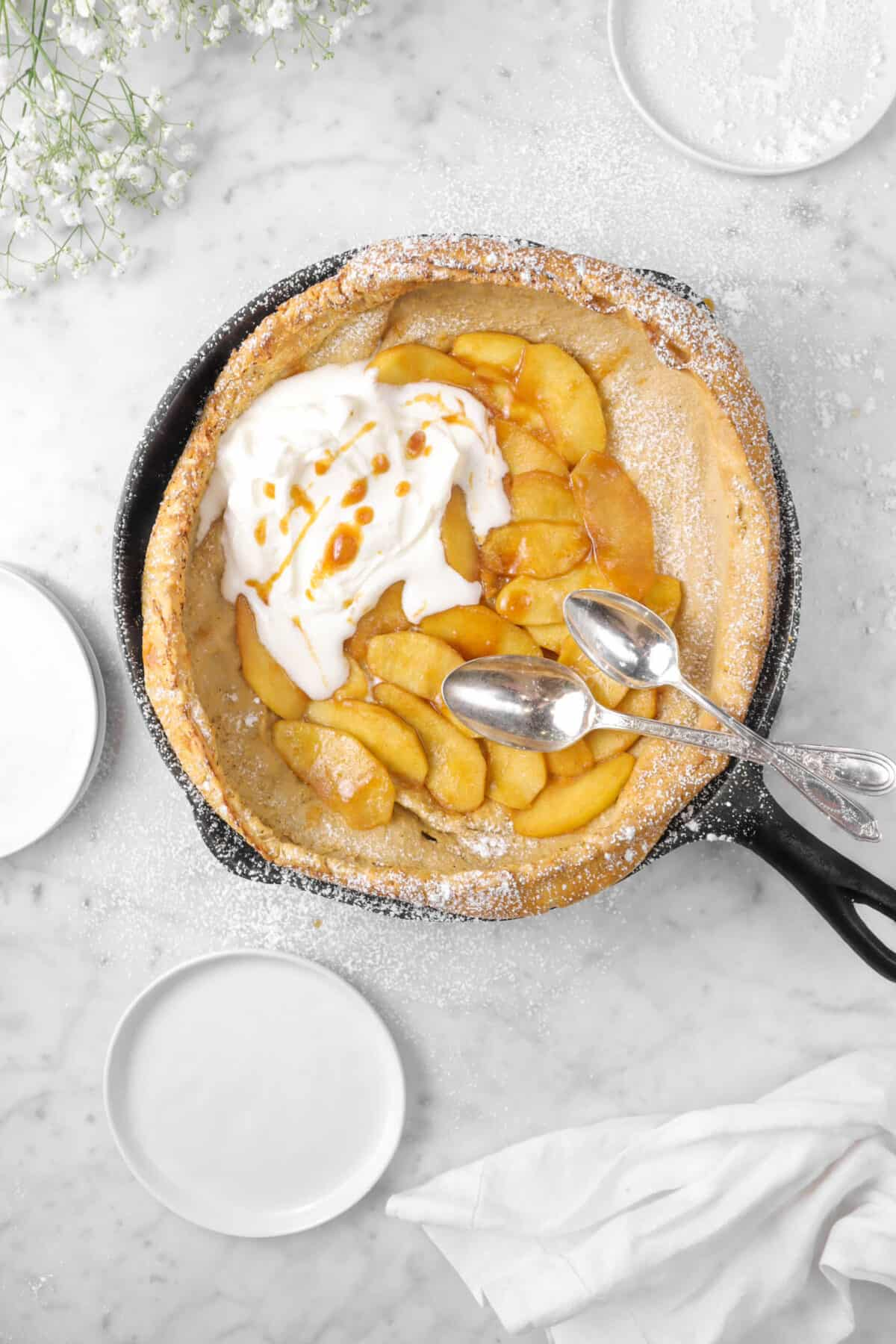 cinnamon apple dutch baby with two spoons in it, three plates, and flowers