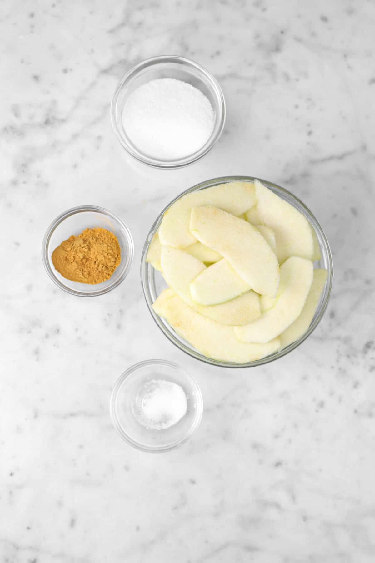 sliced apples, sugar, cinnamon, and salt in bowls