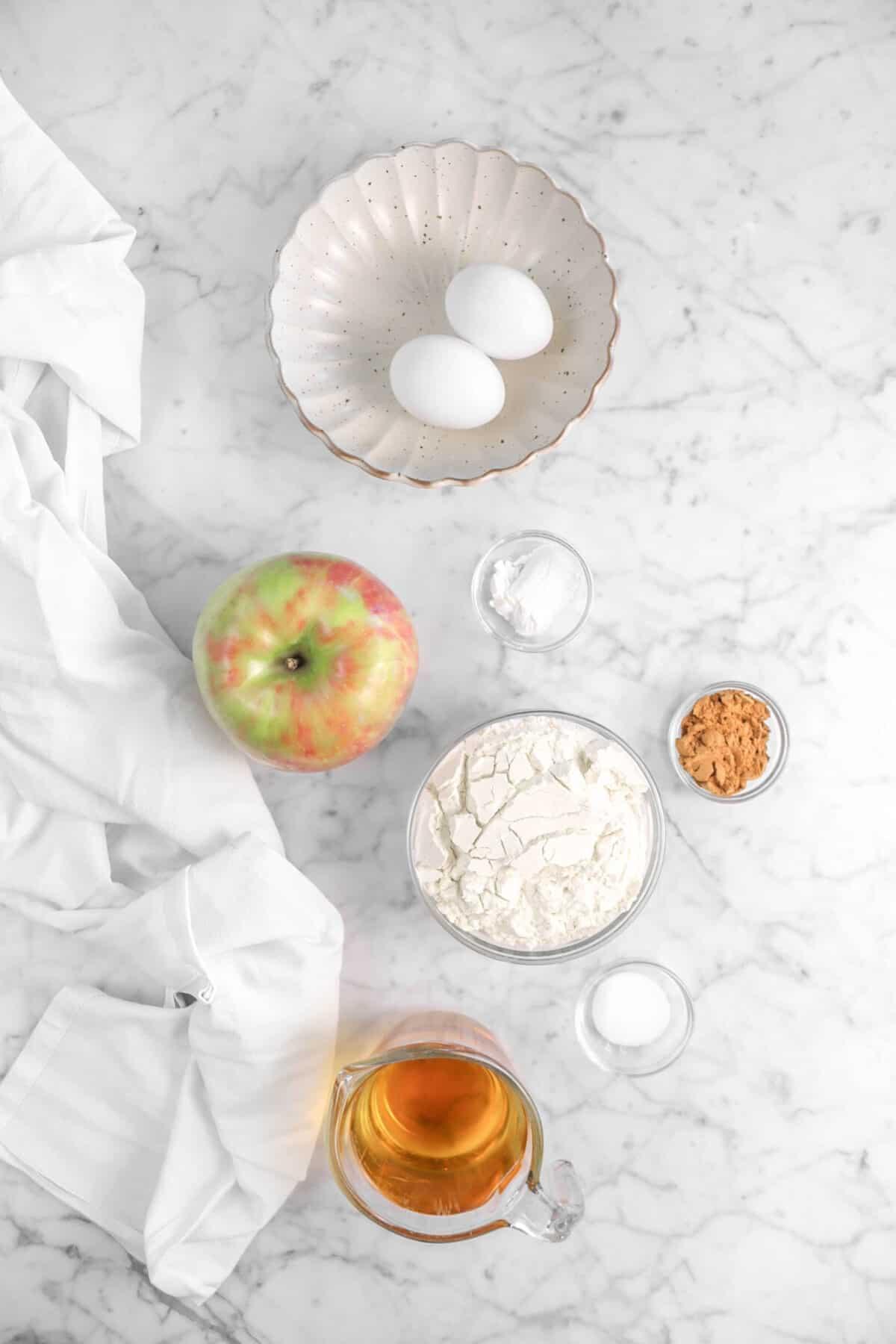 eggs, baking powder, an apple, flour, apple pie spice, salt, and apple juice