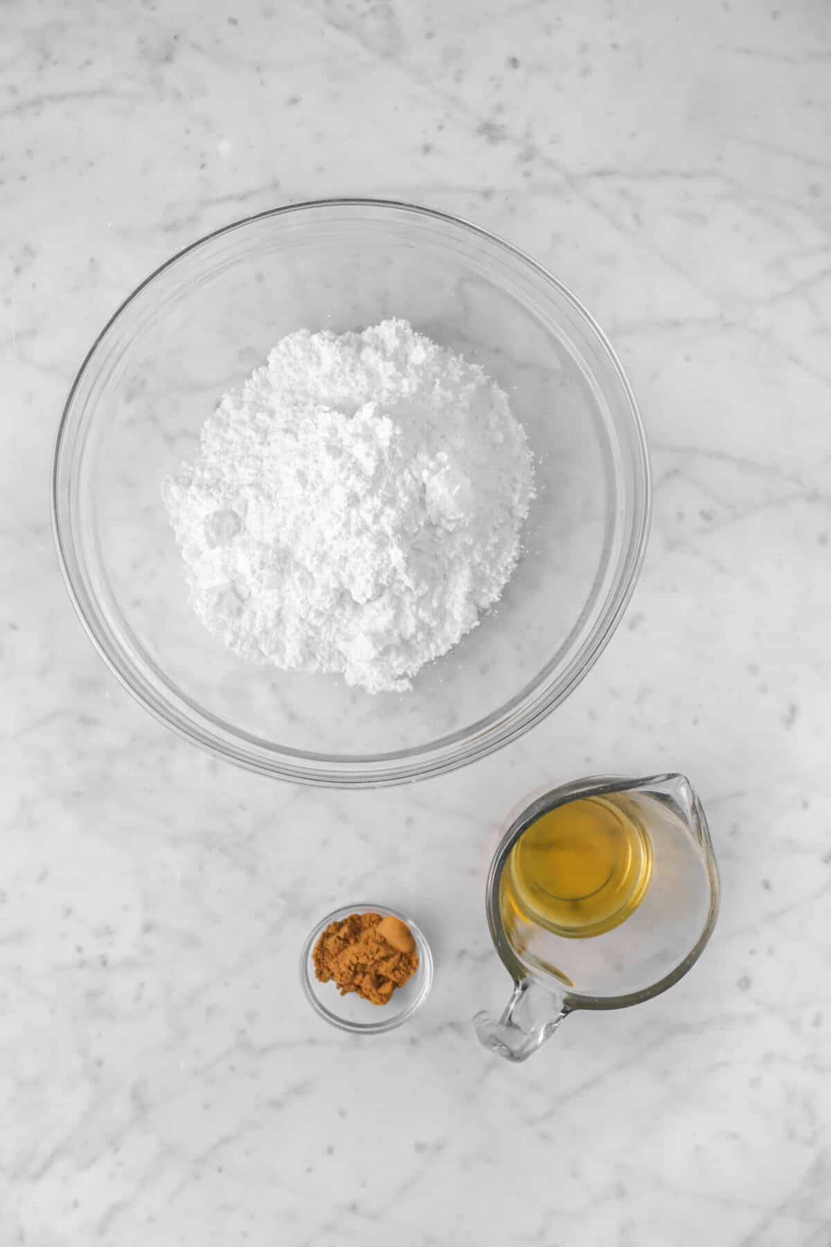 powdered sugar, apple pie spice, and apple juice on marble counter