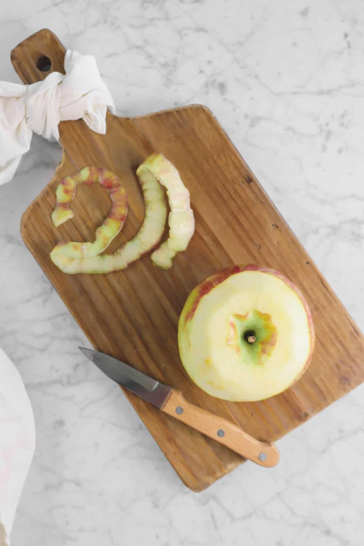 apple slightly peeled on wood board
