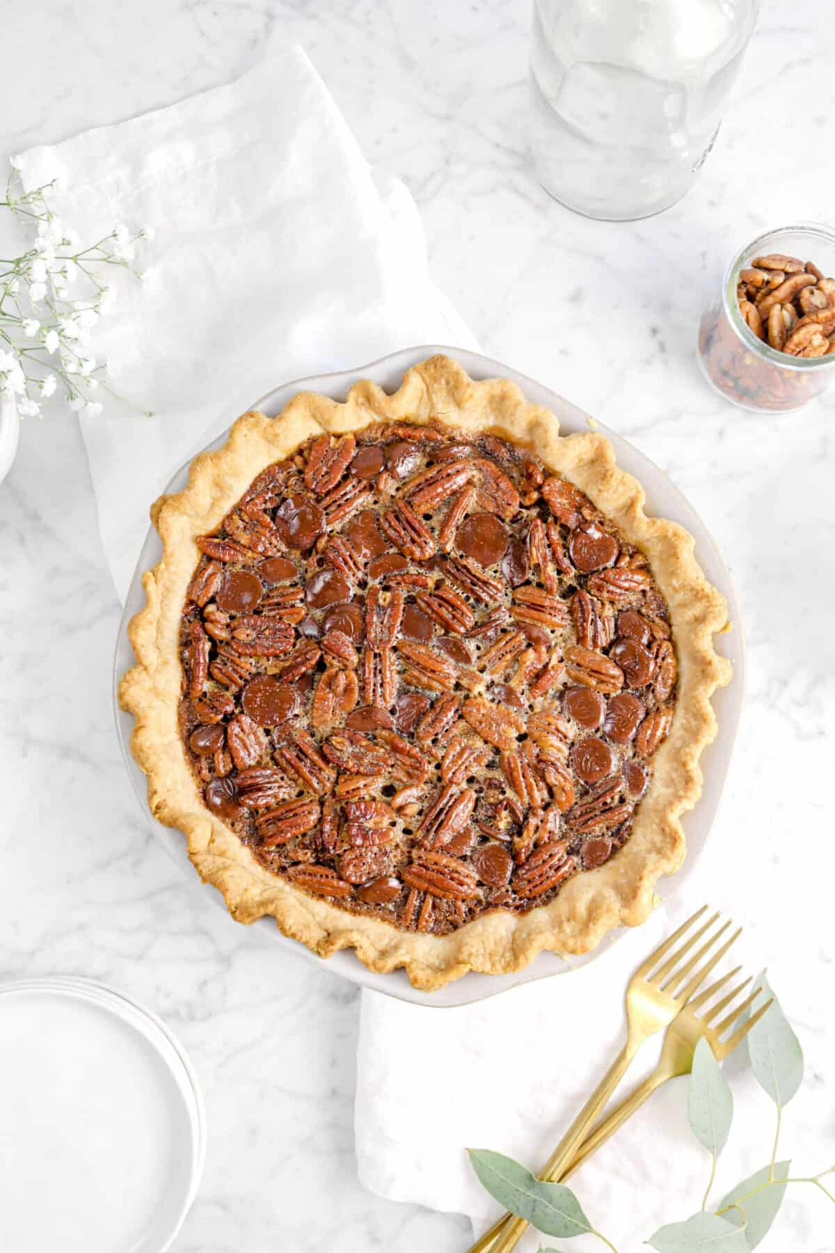 overhead shot of pecan pie on a white napkin with forks, flowers, and jars