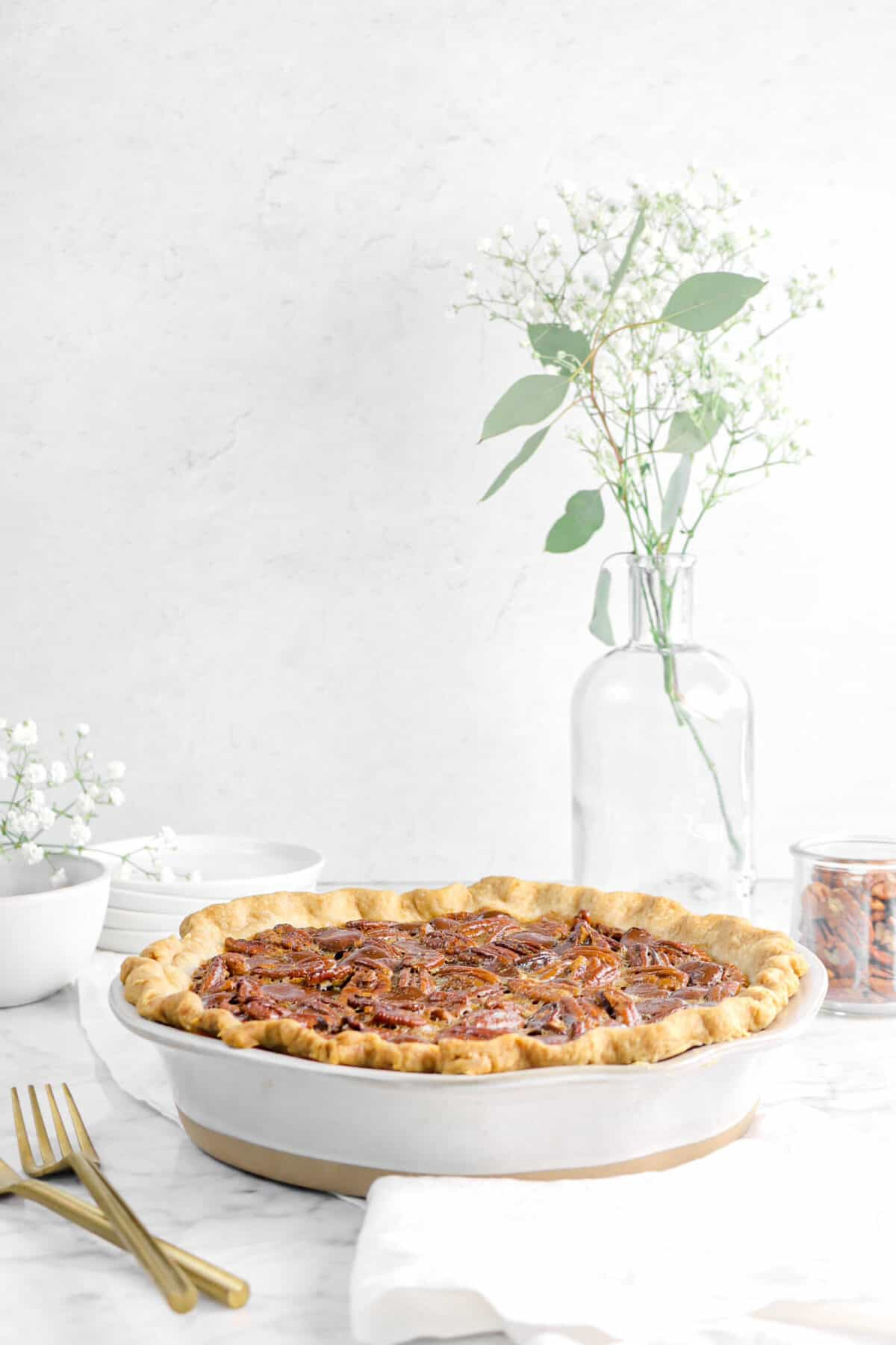 bourbon chocolate pecan pie with flowers, gold forks, plates, and glass jars