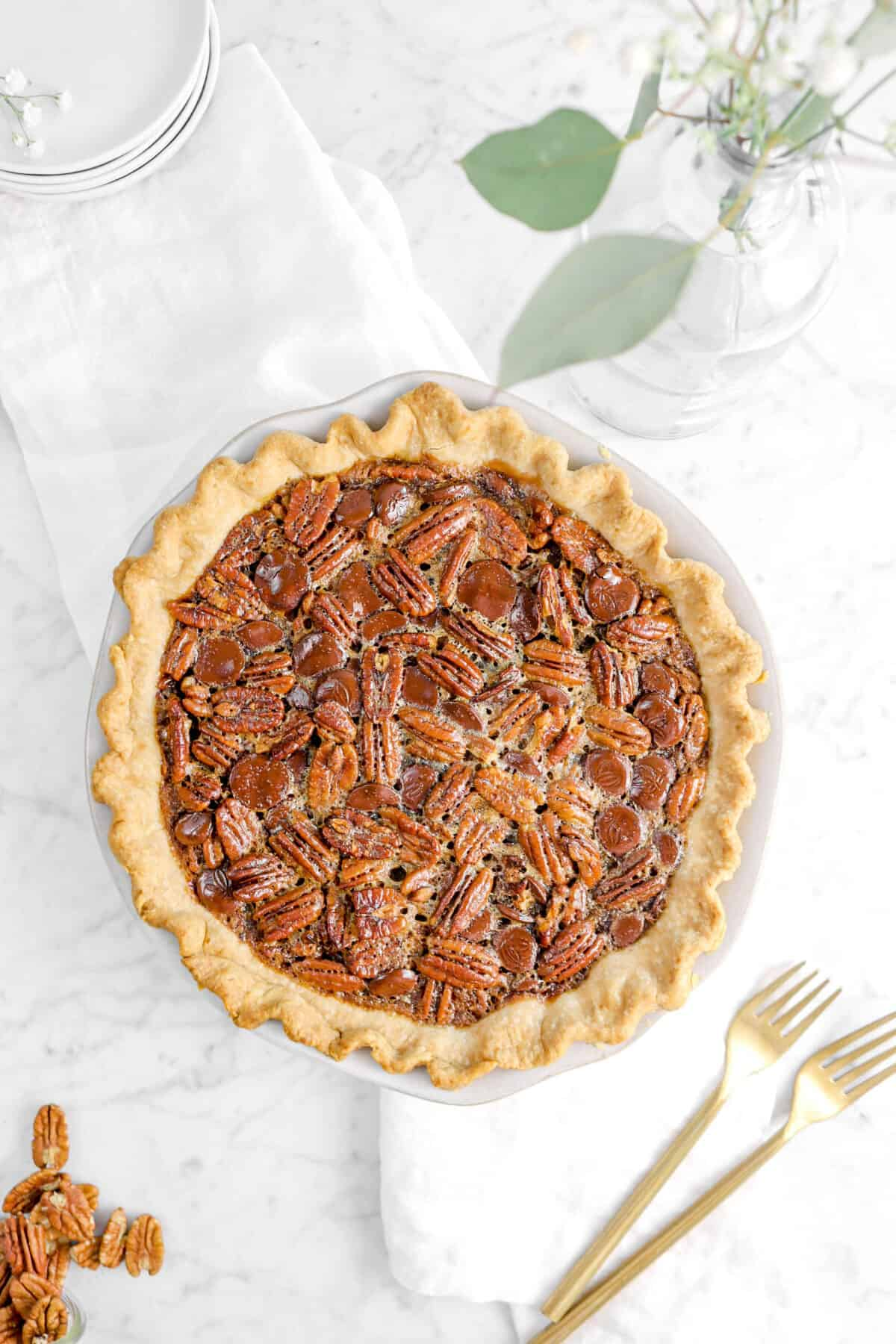 overhead shot of bourbon chocolate pecan pie with two forks and flowers