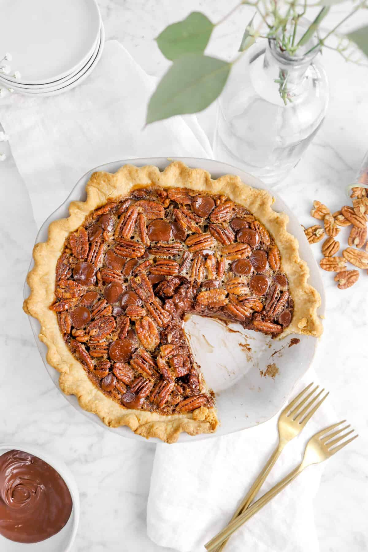 pecan pie with a slice taken out of it, flowers, forks, and pecans