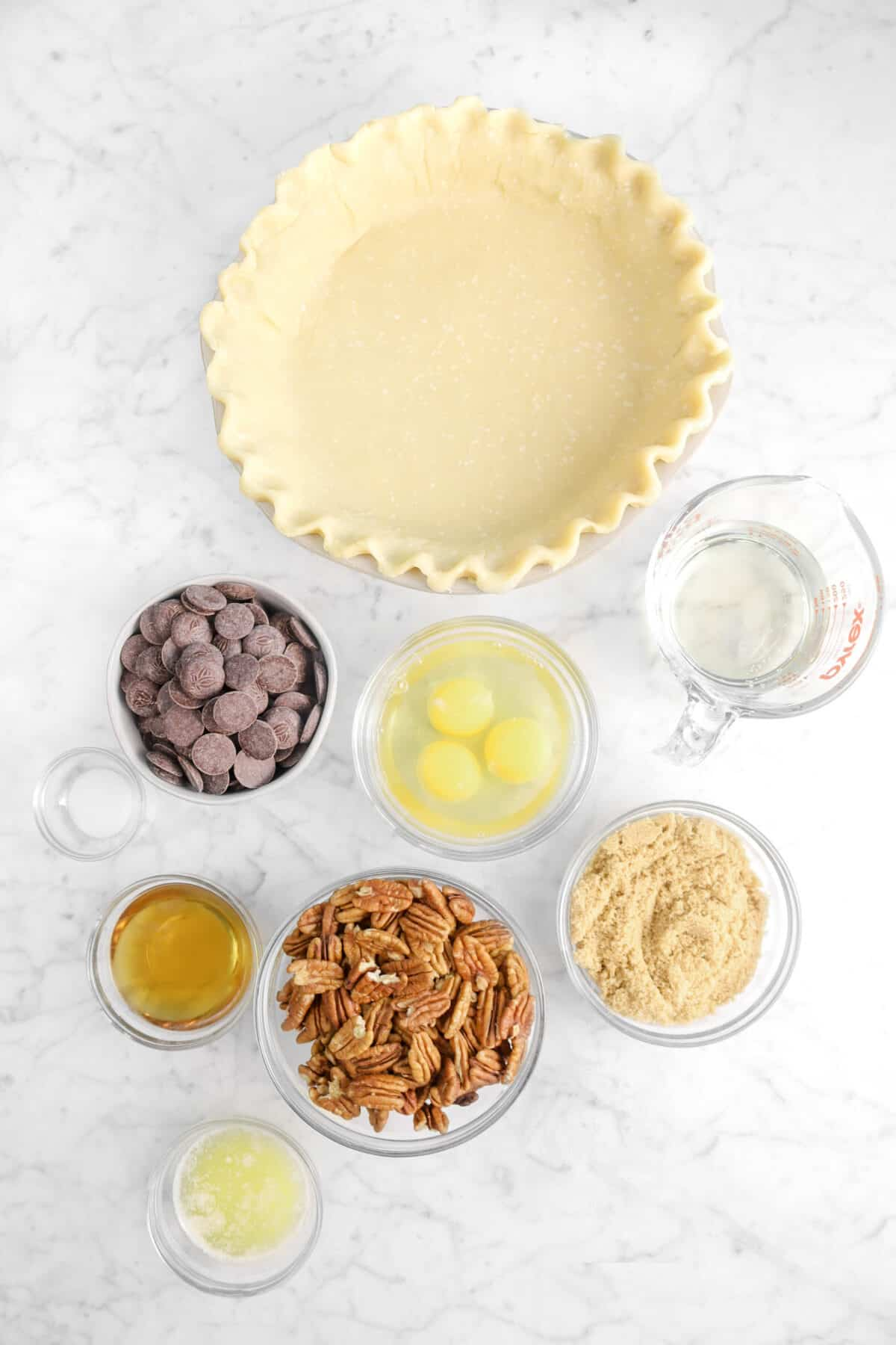 pie crust, corn syrup, chocolate, eggs, brown sugar, pecans, salt, bourbon, and melted butter on marble counter