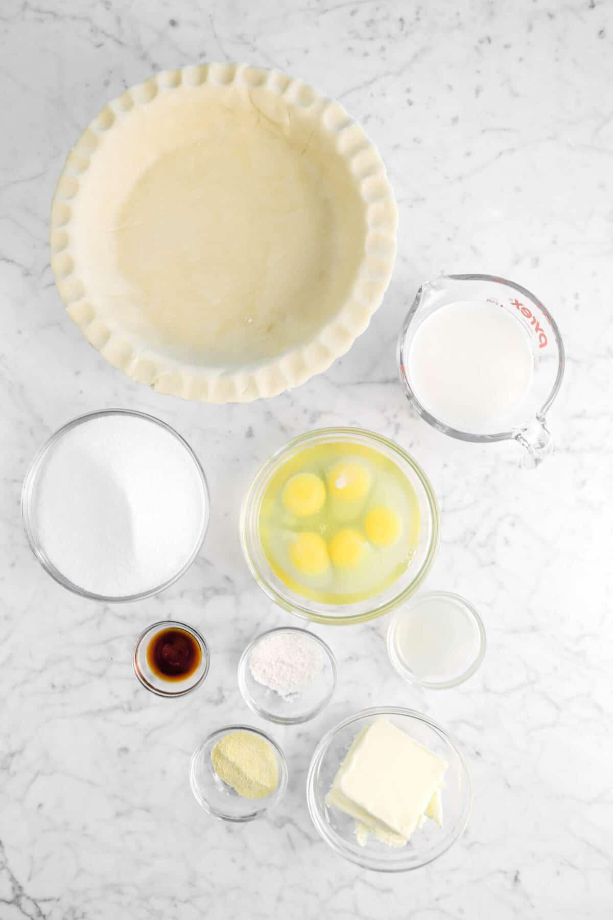 pie crust, milk, eggs, sugar, vanilla, flour, lemon juice, cornmeal, and butter on a marble counter