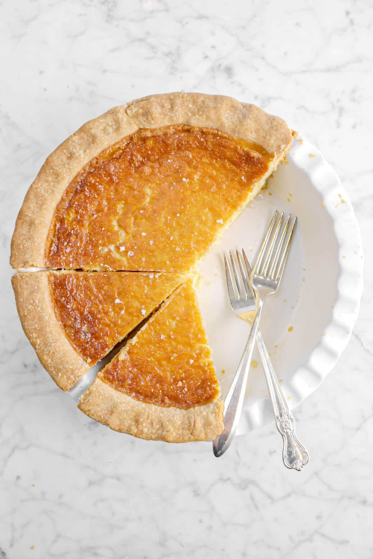 chess pie in a white pie plate with two forks and slices taken out of it