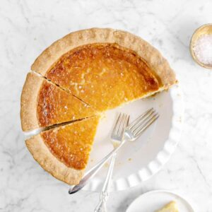 chess pie with two forks, four slices taken out of it, and whipped cream