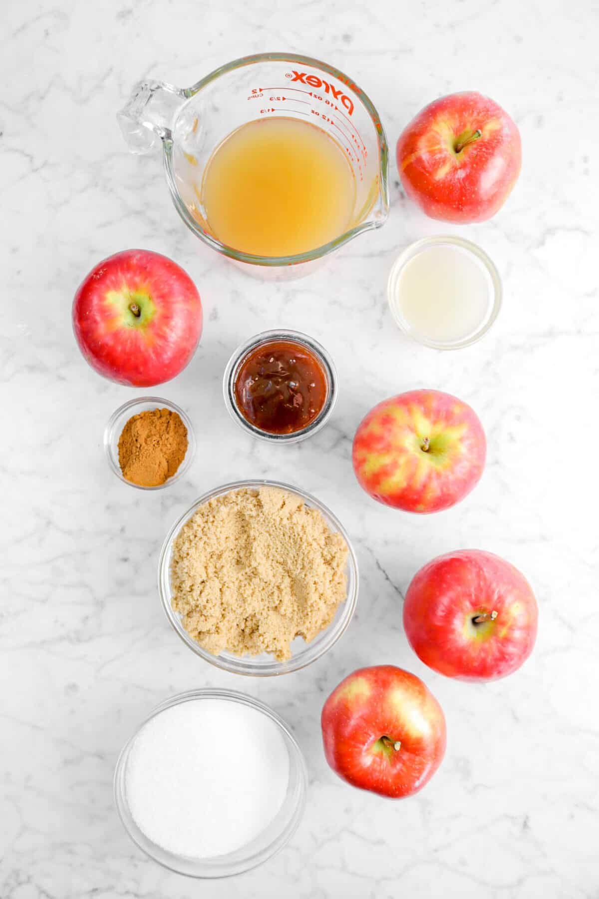 apple cider, apples, lemon juice, boiled cider, apple pie spice, brown sugar, and sugar on a marble counter