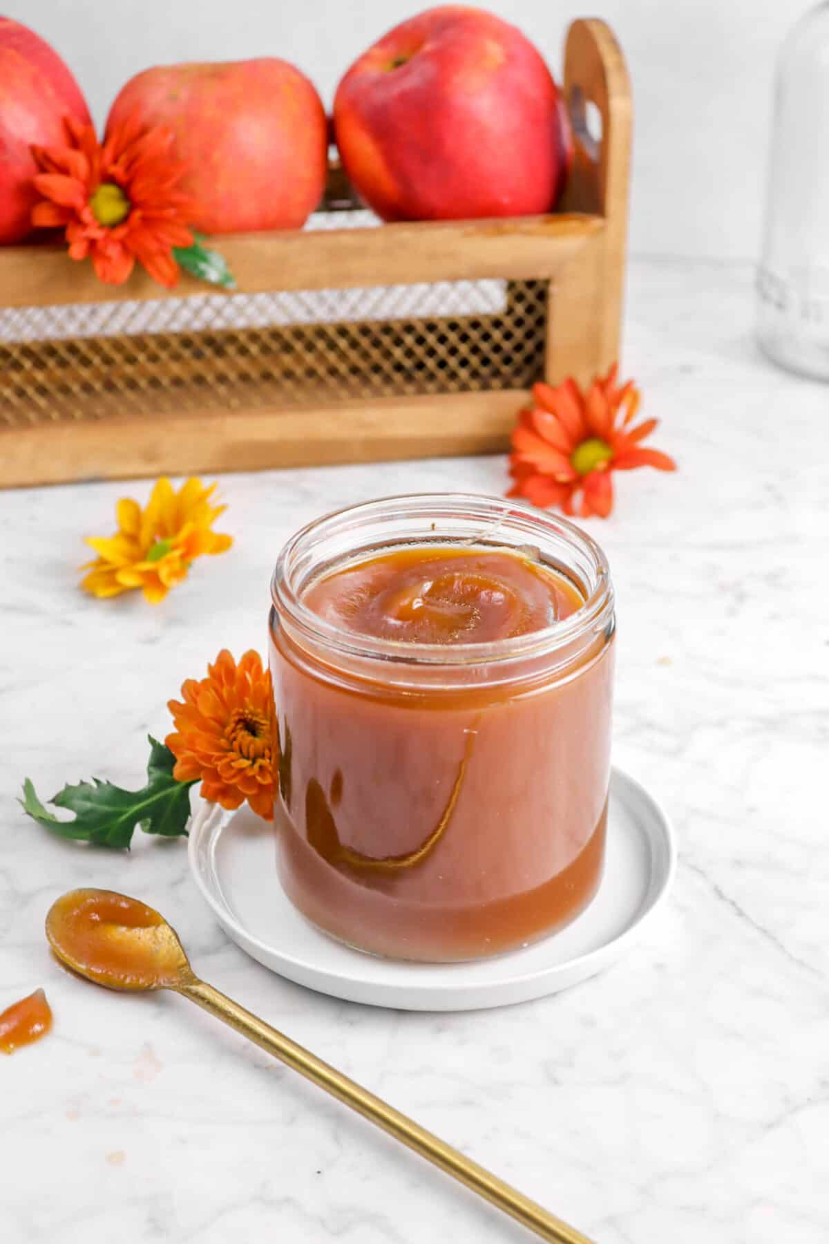 apple butter in a jar with flowers, a white plate, a gold spoon, and apples behind