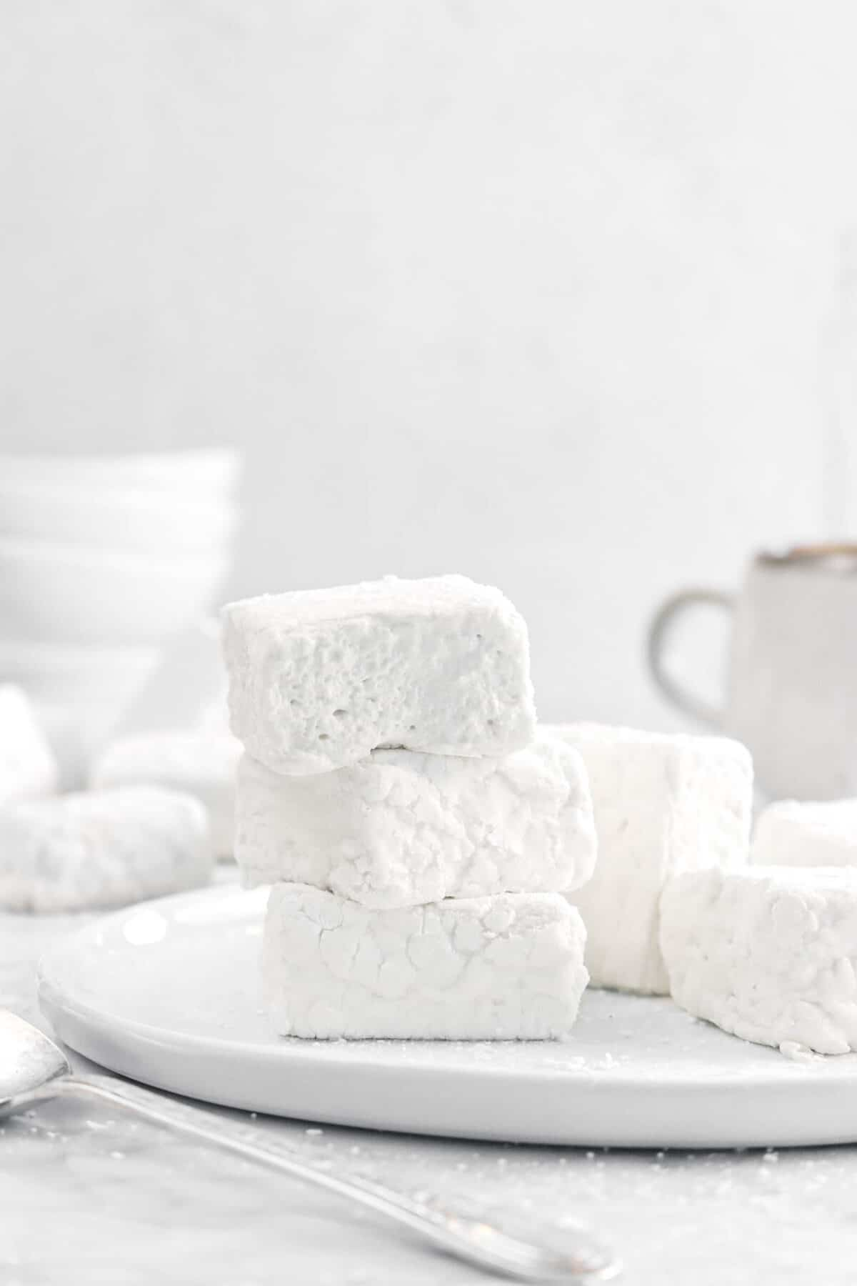 three marshmallows stacked on a white plate with more behind