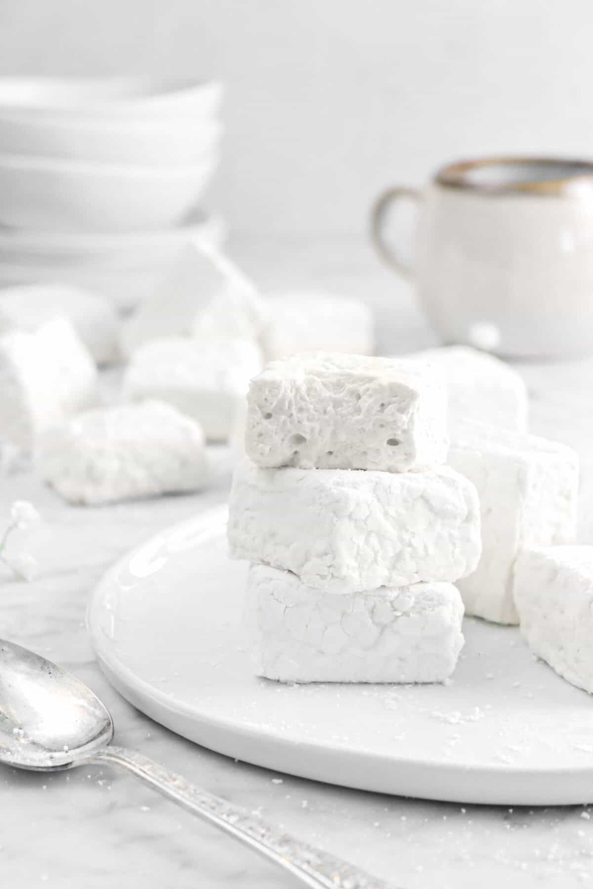 three stacked marshmallows on a white plate with a mug and plates behind