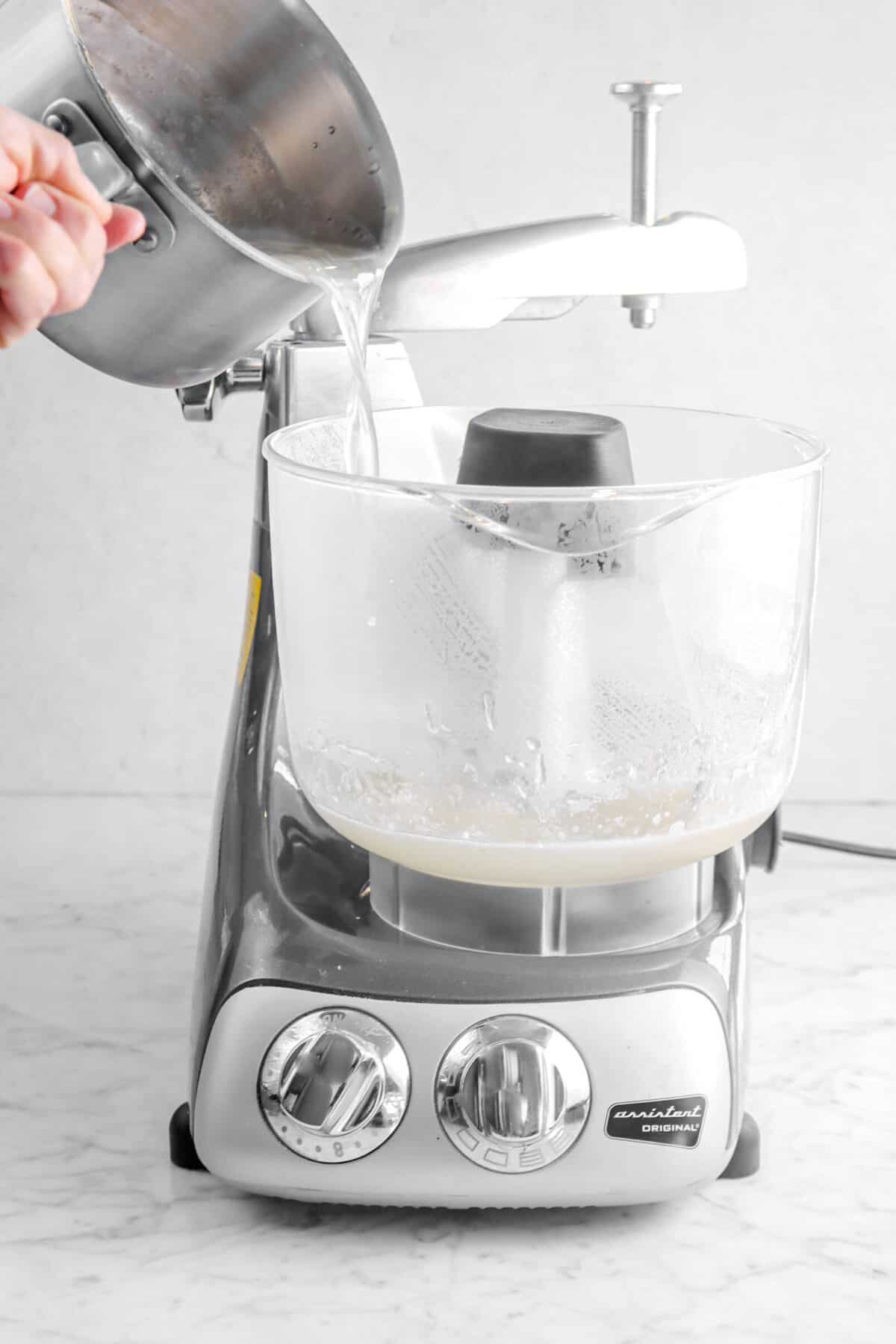 melted sugar mixture being poured into mixer