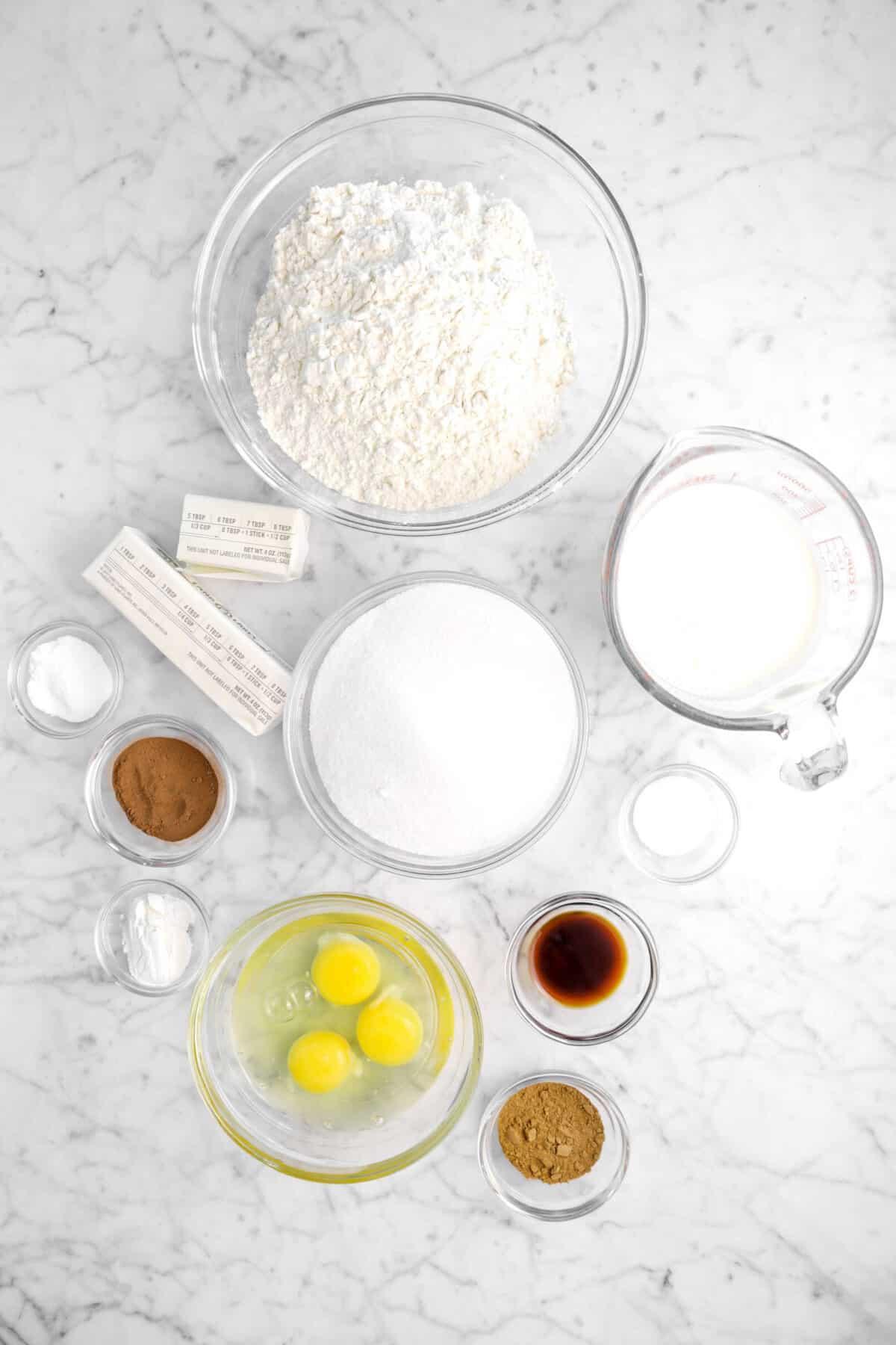 flour, butter, baking soda, cocoa, baking powder, sugar, eggs, milk, salt, vanilla, and pumpkin pie spice on marble counter