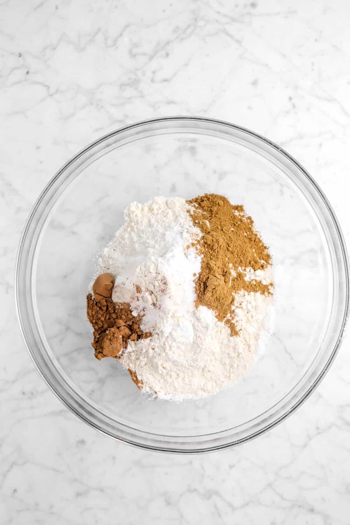 flour, baking powder, baking soda, cocoa powder, and pumpkin pie spice in a glass bowl