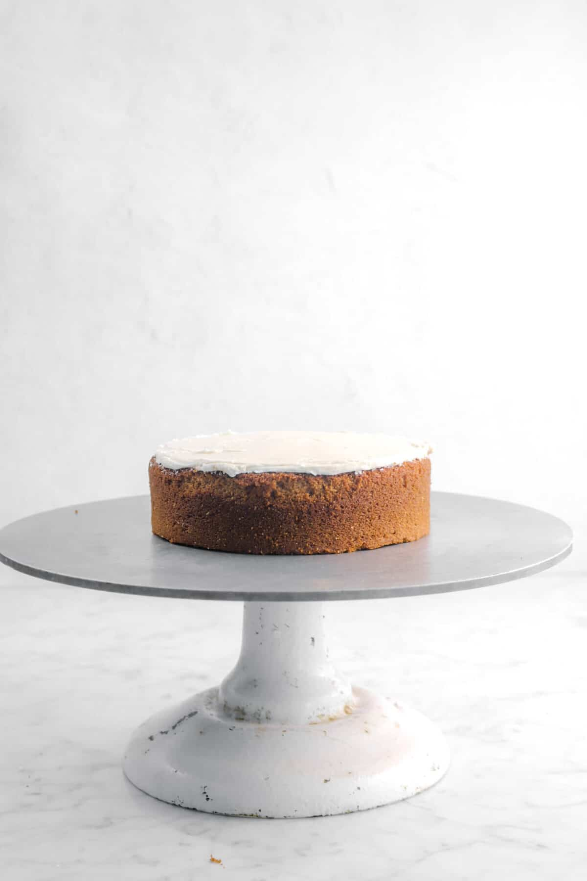 frosting spread on cake layer on a cake stand
