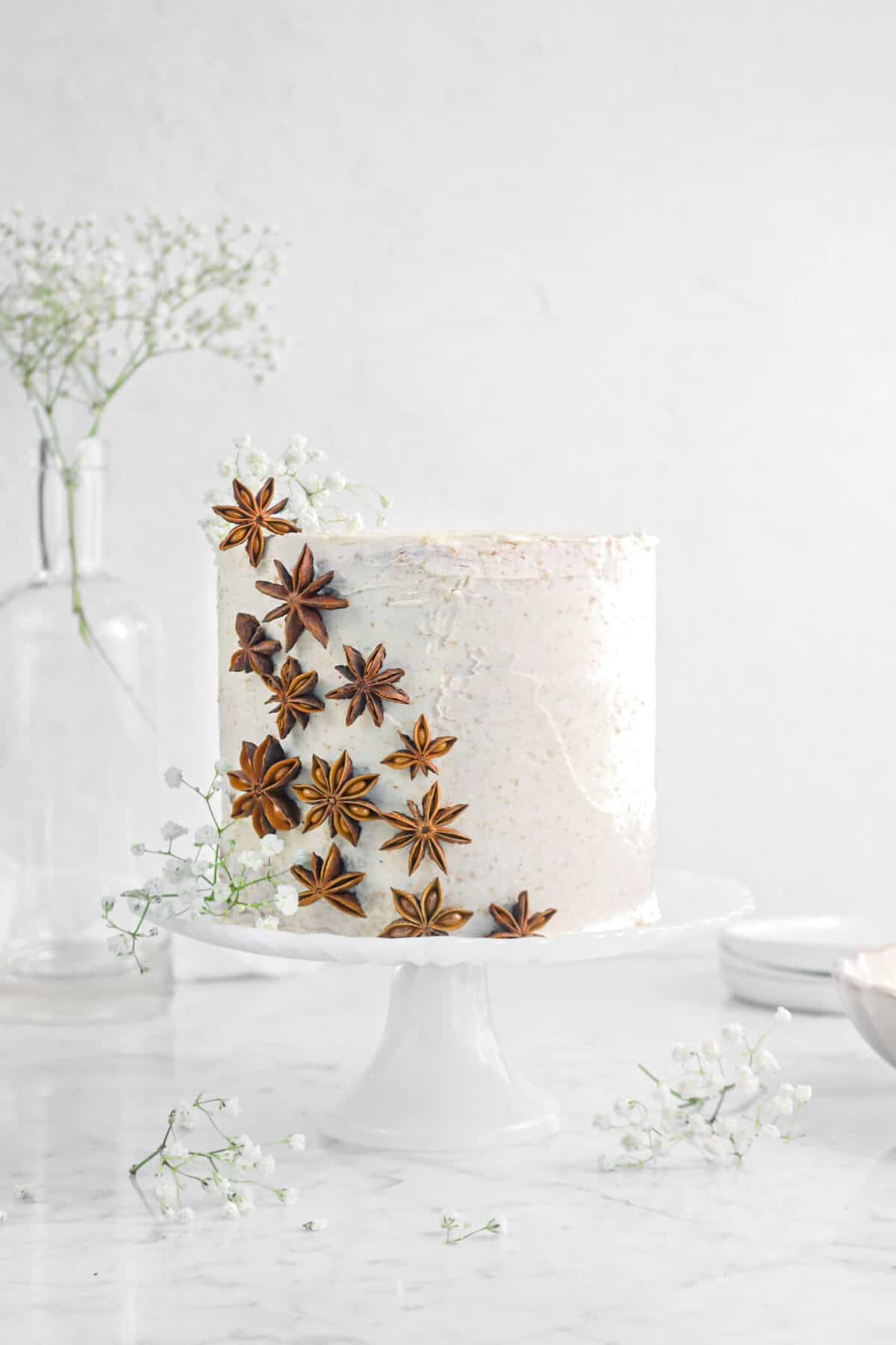 spice cake on cake stand with star anise and flowers