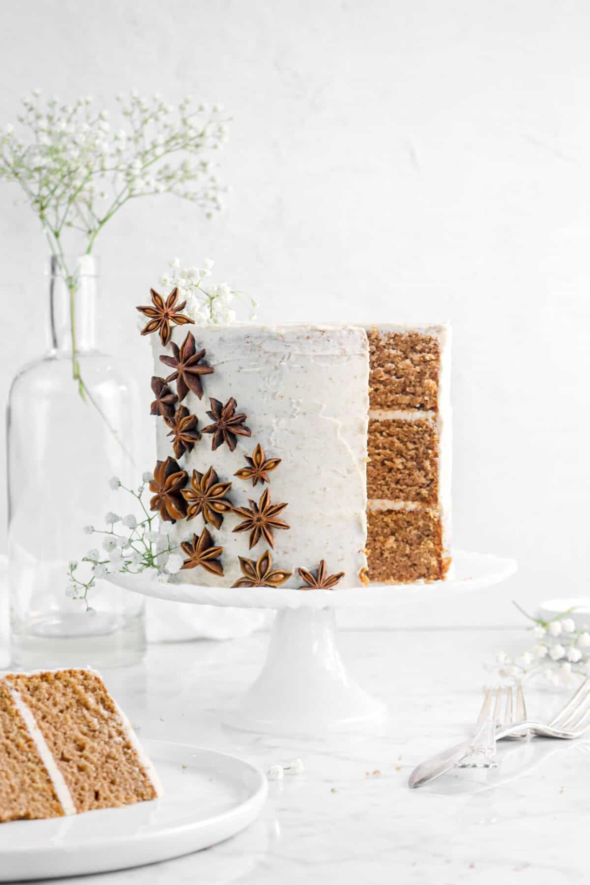 spice cake with a slice out of it with flowers, star anise, and slice on a white plate