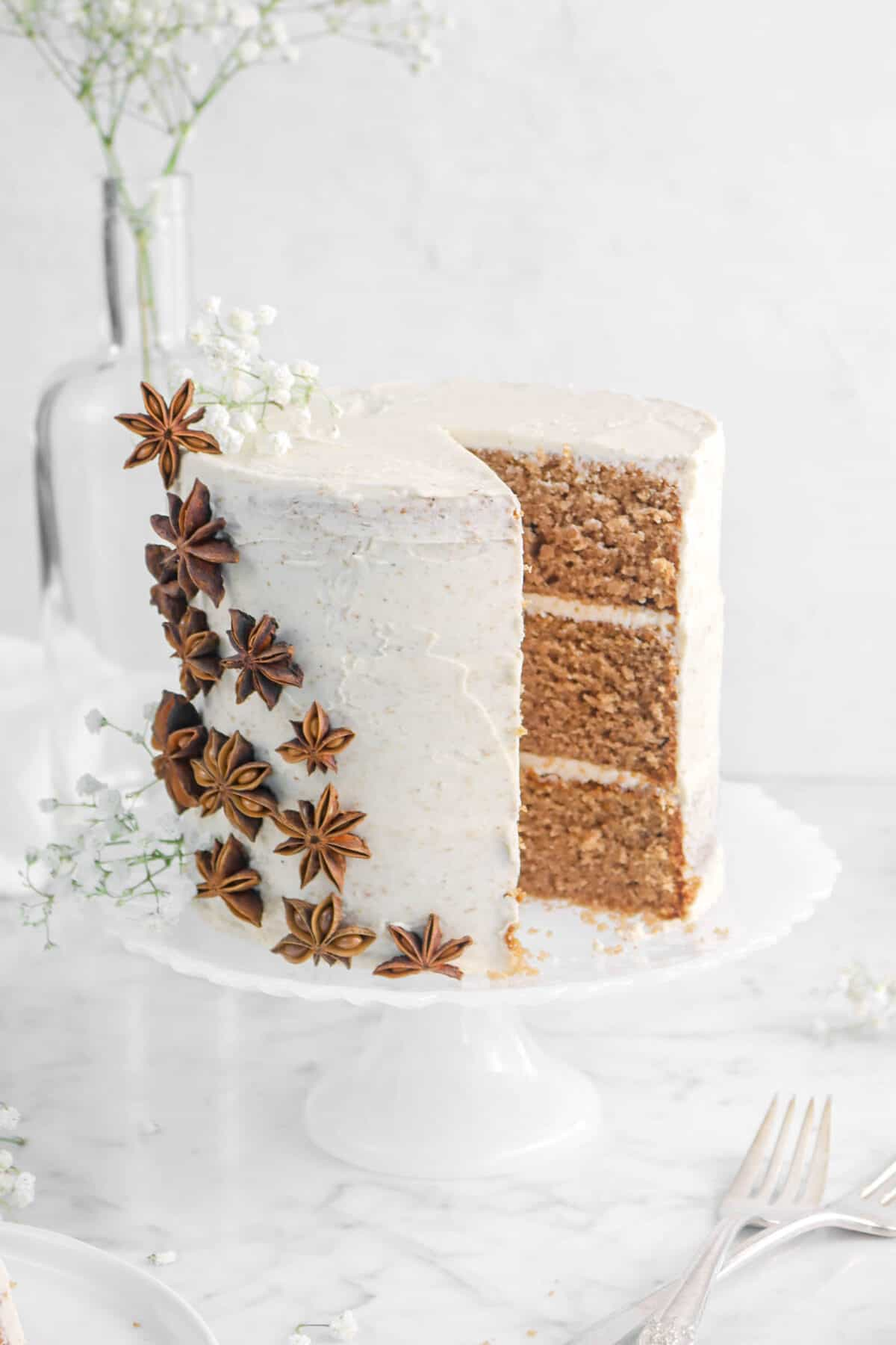 pumpkin spice cake on a white cake plate with a slice taken out of it