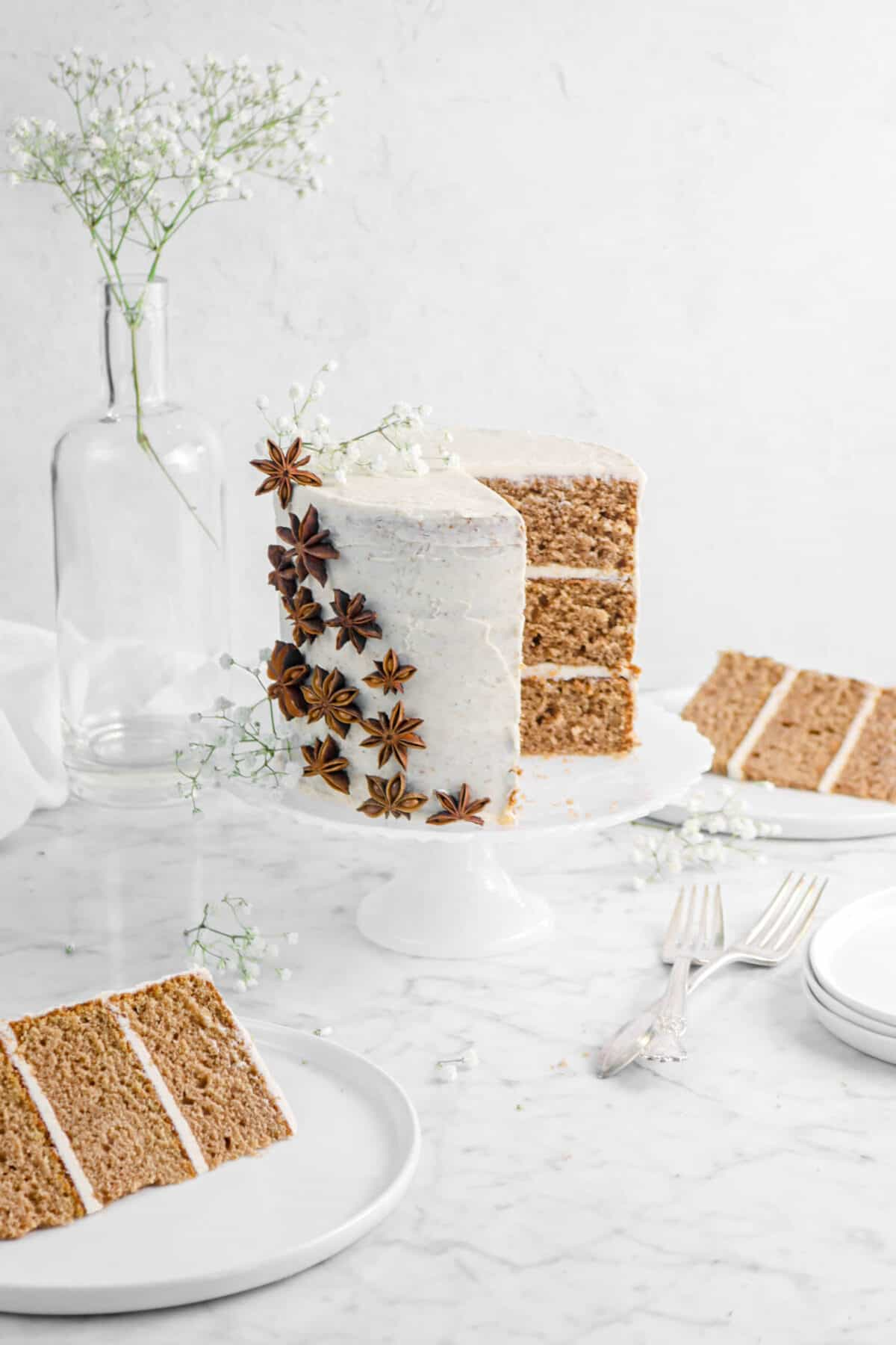 spice cake on white cake plate with slice slices, flowers, and star anise
