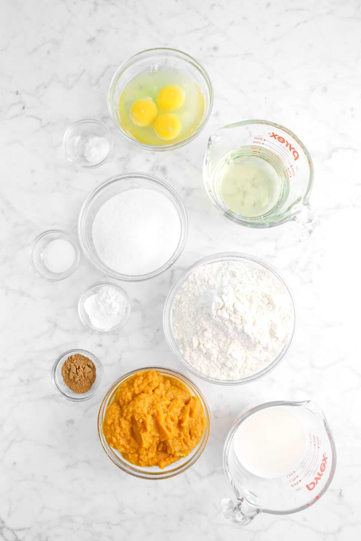 eggs, baking powder, vegetable oil, sugar, salt, baking soda, flour, pumpkin pie spice, vegetable oil, milk in bowls on marble counter