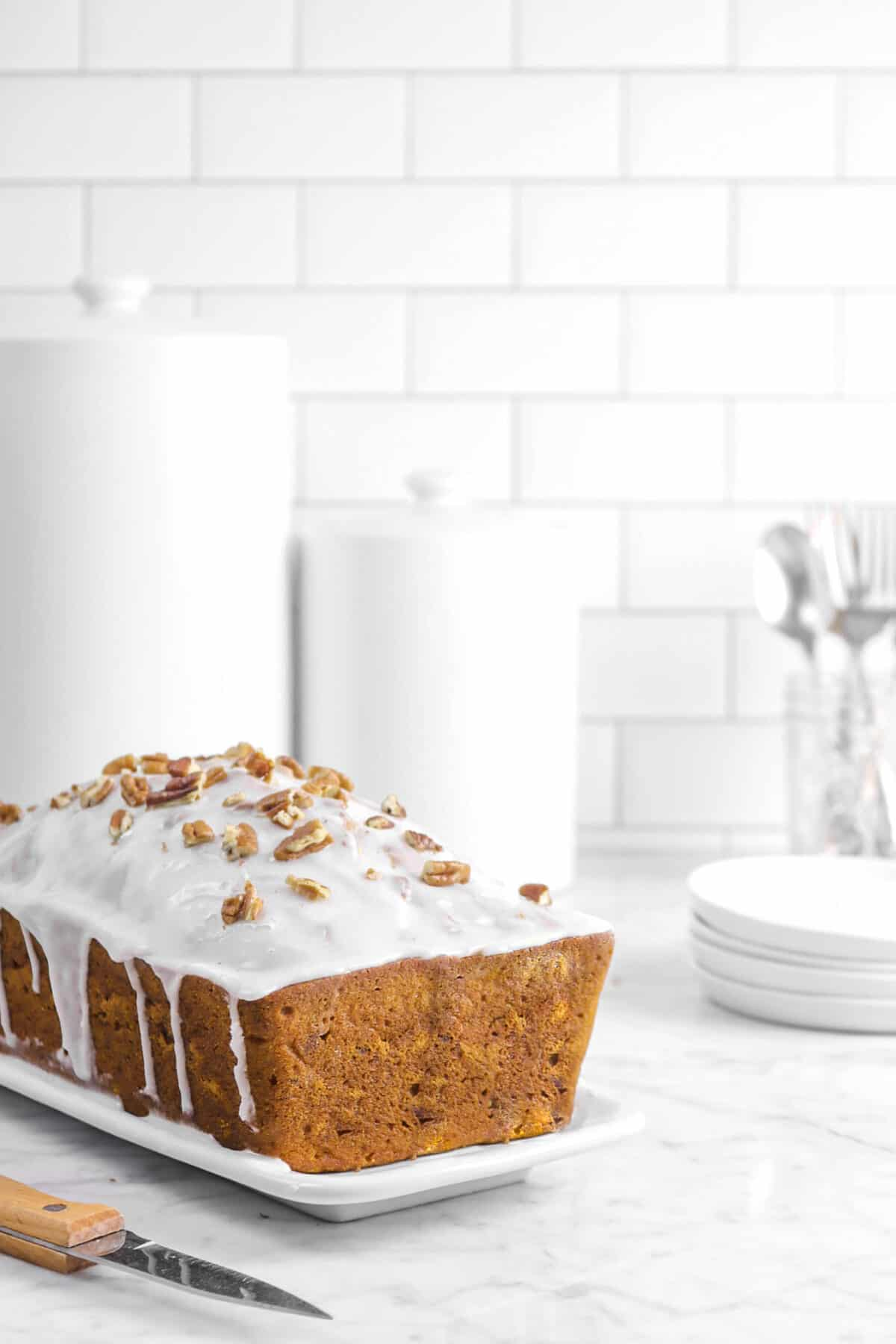 pumpkin bread on a white plate with plates, forks, and jars behind