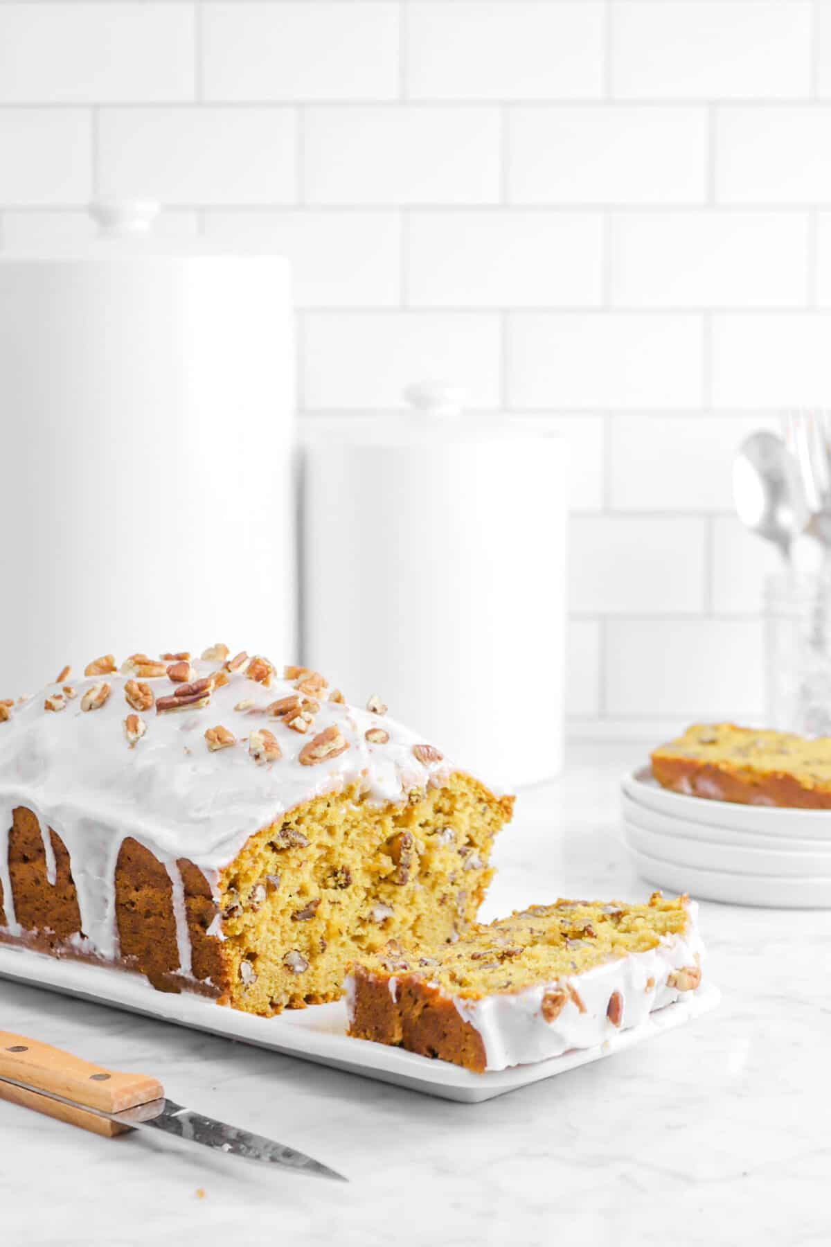 pumpkin bread on a white plate with a slice laying in front of it with plates and containers behind