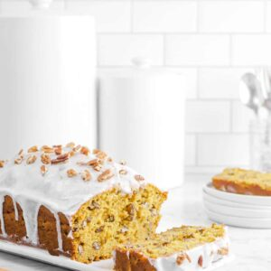 pumpkin pecan bread with glaze on a white plate, with a slice behind, two jars, and a knire