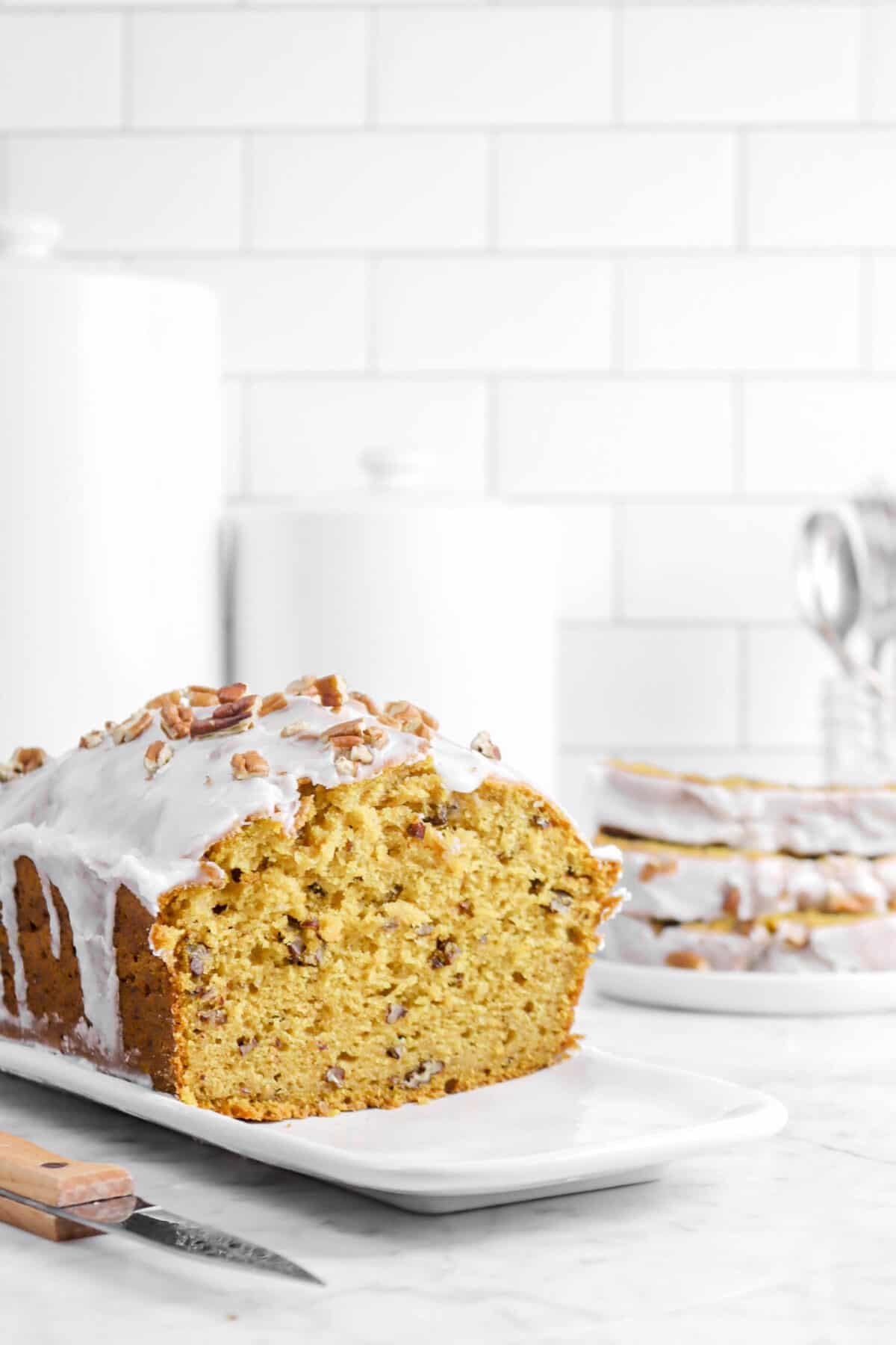 pumpkin bread with three slices stacked behind with a knife, forks, and white containers