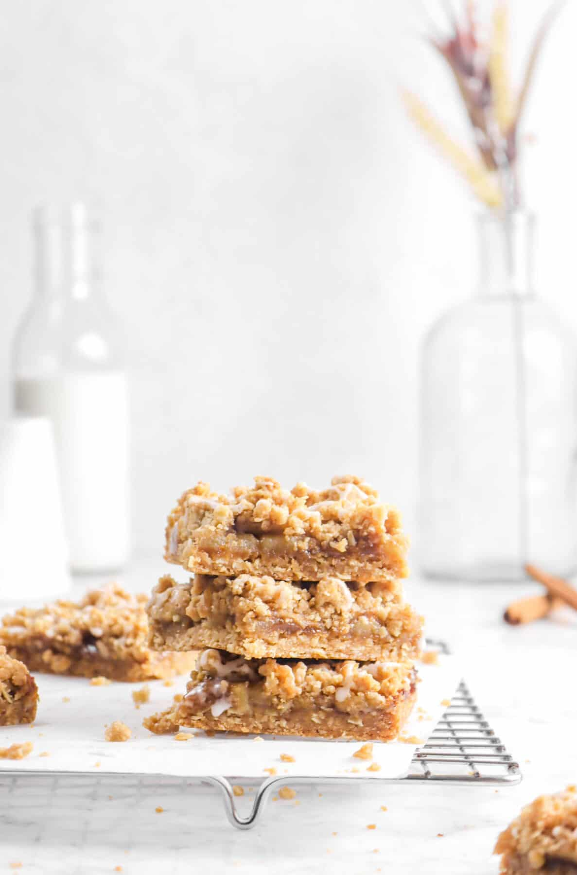 three apple pie crumble bars stacked on wire cooling rack