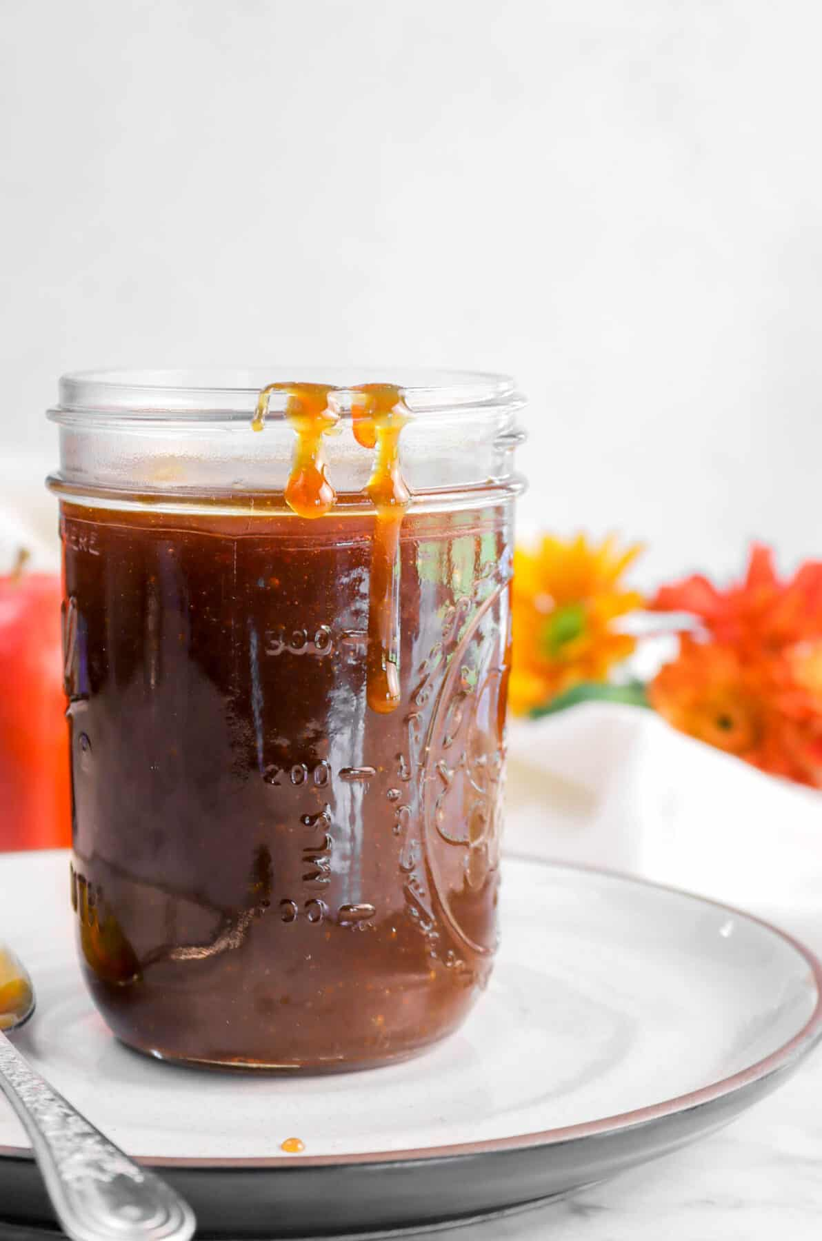 boiled cider in a jar on a white plate with flowers